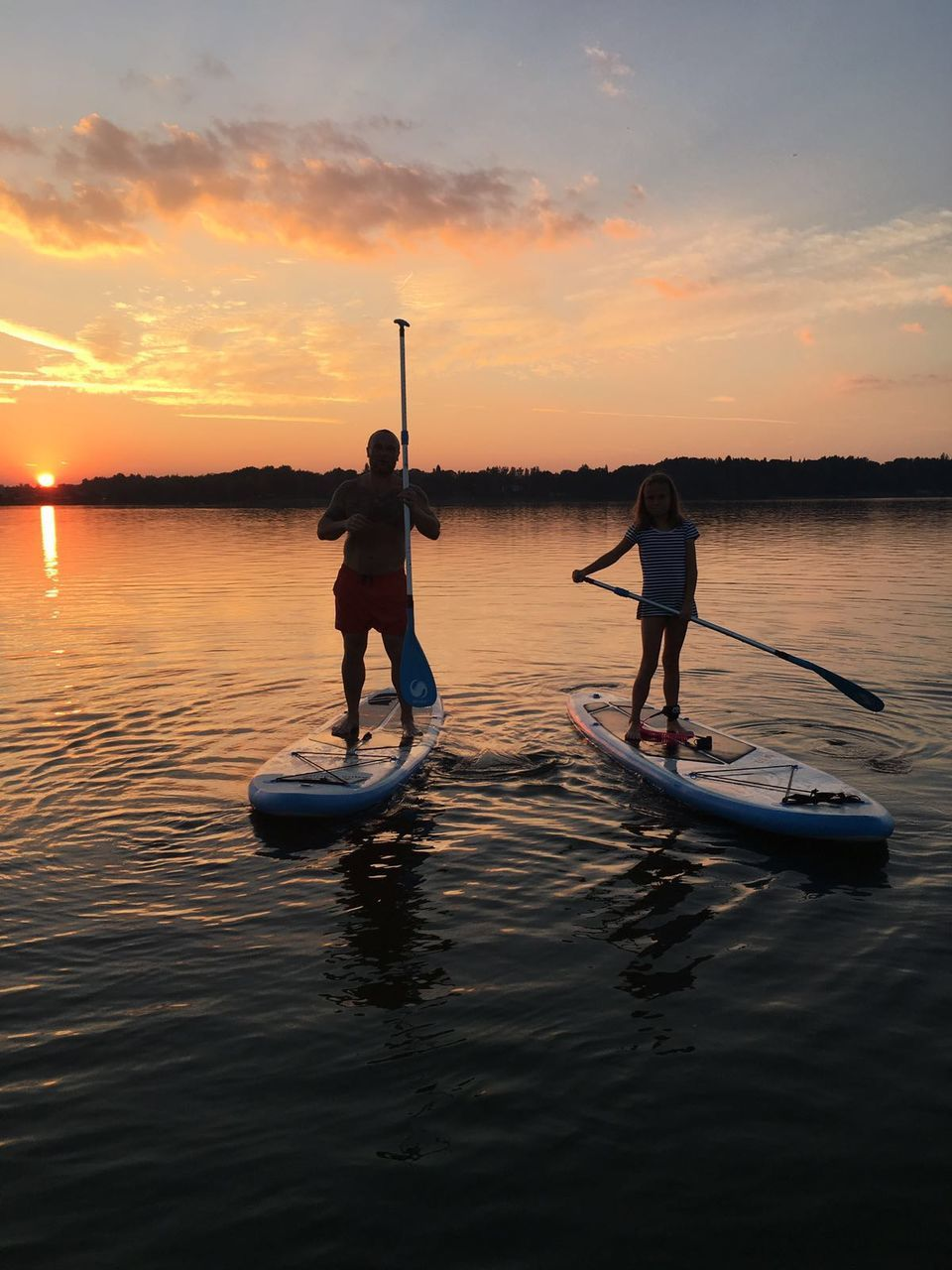 sunset, water, nature, real people, two people, beauty in nature, sky, men, cloud - sky, silhouette, leisure activity, scenics, waterfront, nautical vessel, transportation, full length, standing, outdoors, lifestyles, togetherness, sea, paddleboarding, people