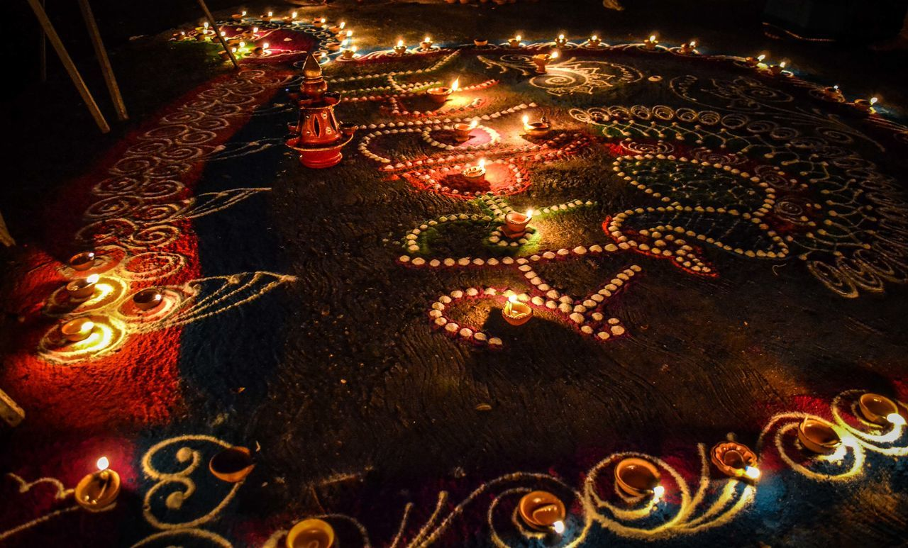High Angle View Of Lit Diyas On Rangoli Pattern During Diwali