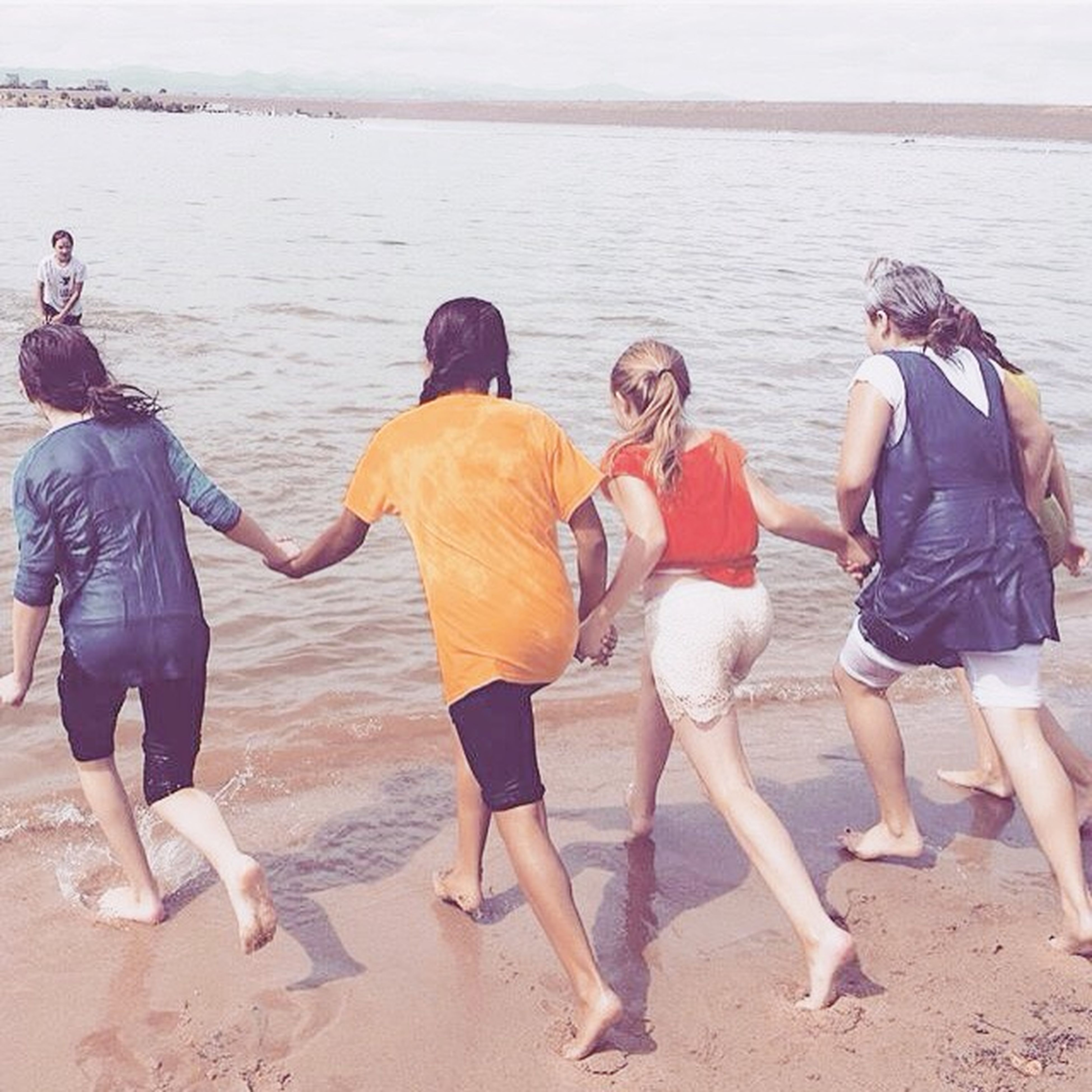 water, togetherness, lifestyles, sea, leisure activity, beach, bonding, vacations, shore, men, friendship, love, sand, casual clothing, full length, person, large group of people, enjoyment
