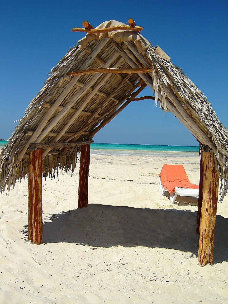 sand, beach, nature, sunlight, shore, sea, wood - material, shadow, clear sky, day, thatched roof, outdoors, beauty in nature, shelter, tranquility, no people, scenics, horizon over water, sky, water