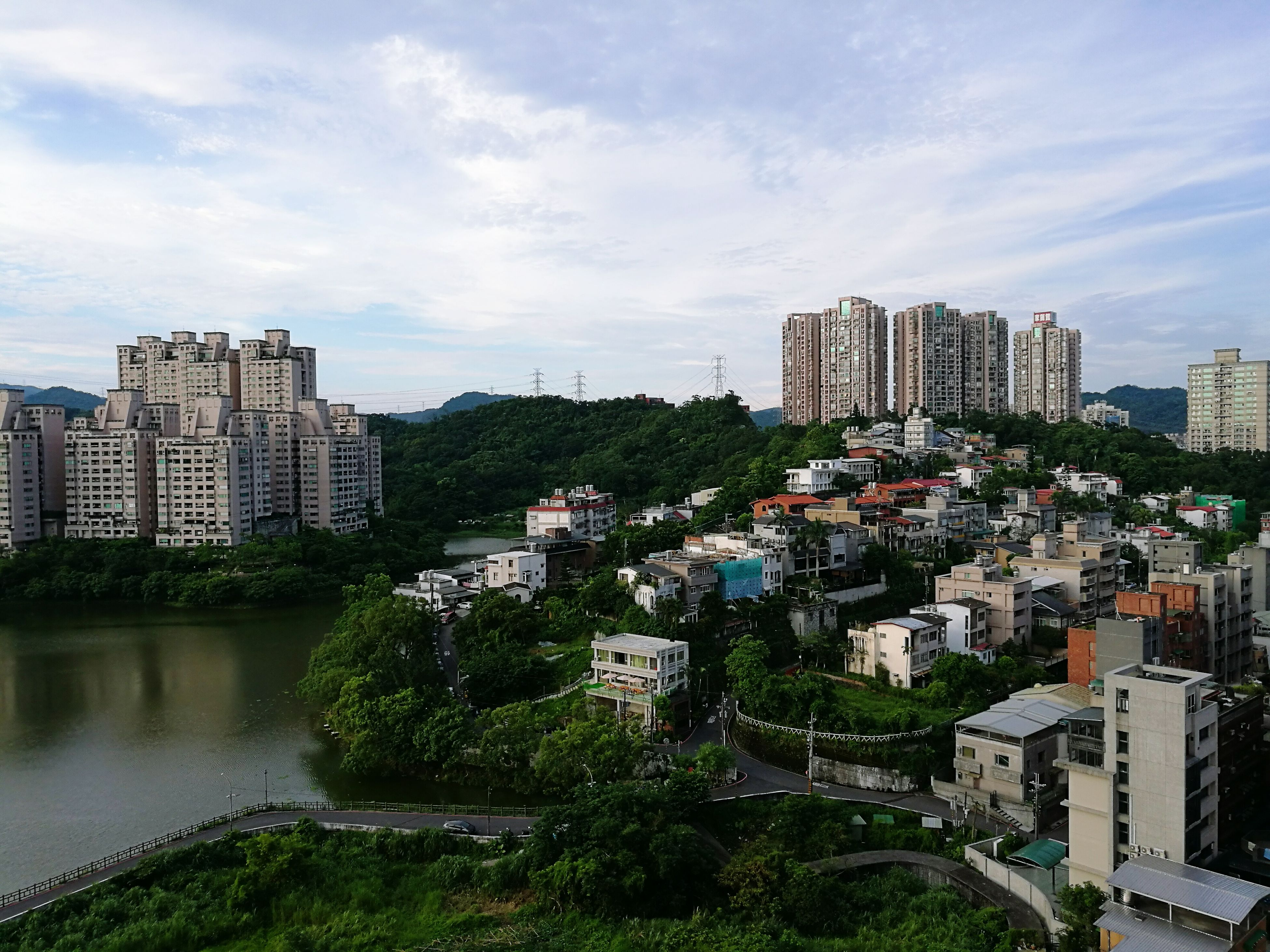 building exterior, architecture, built structure, city, sky, cityscape, tree, water, cloud - sky, residential district, residential building, skyscraper, high angle view, residential structure, river, cloud, crowded, city life, cloudy, growth