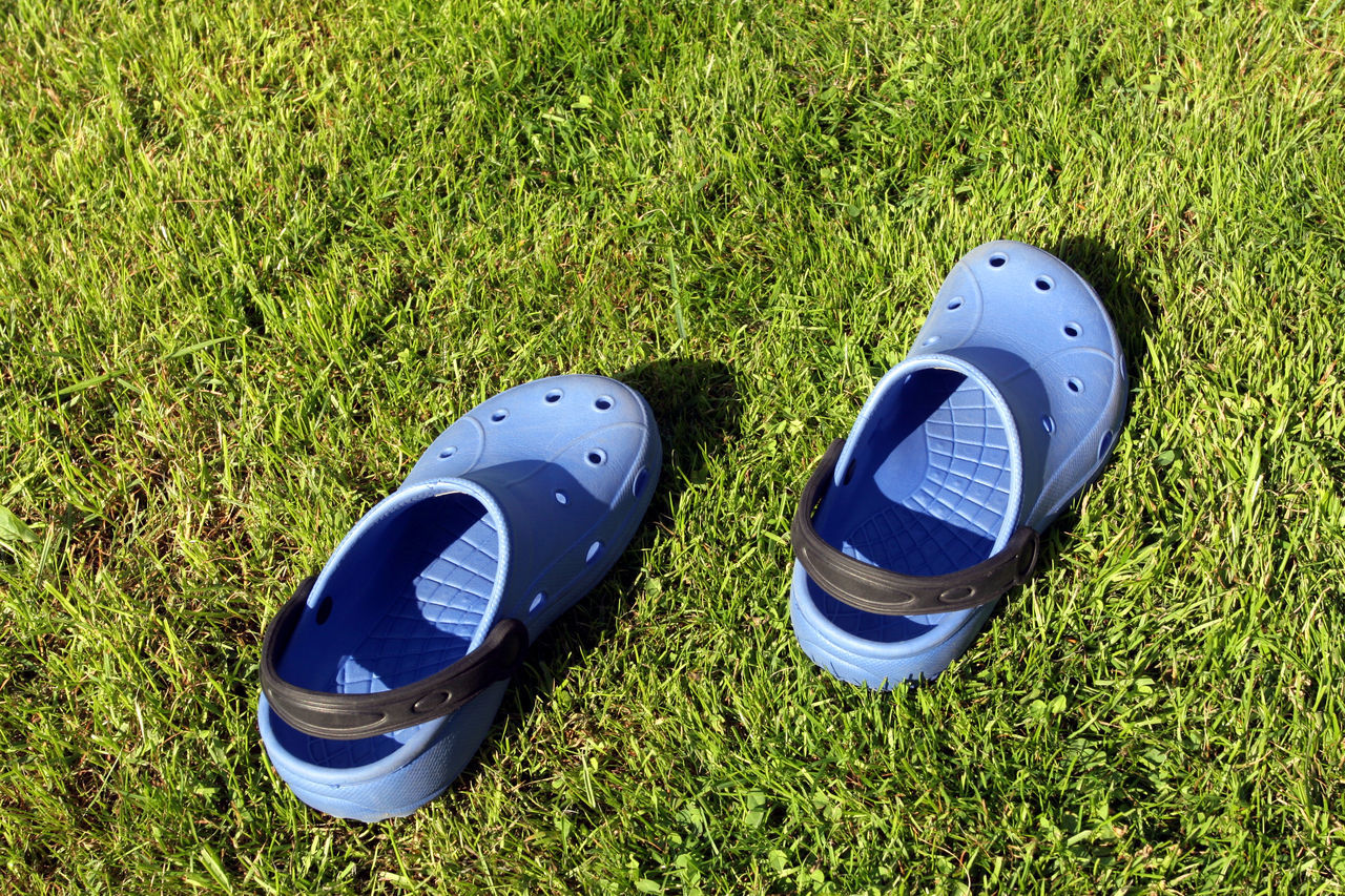 grass, high angle view, blue, pair, green color, day, shoe, outdoors, growth, no people, sport, beach, american football - sport, competitive sport, nature