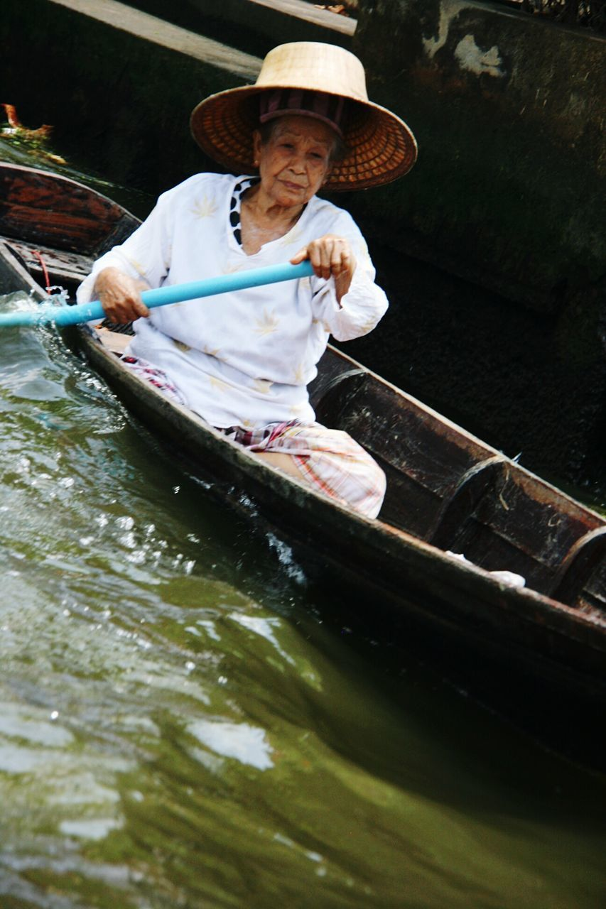 hat, nautical vessel, water, transportation, asian style conical hat, oar, real people, boat, one person, sun hat, outdoors, rowing, river, day, gondolier, rowboat, lifestyles, sitting, nature, gondola - traditional boat, women, young adult, people