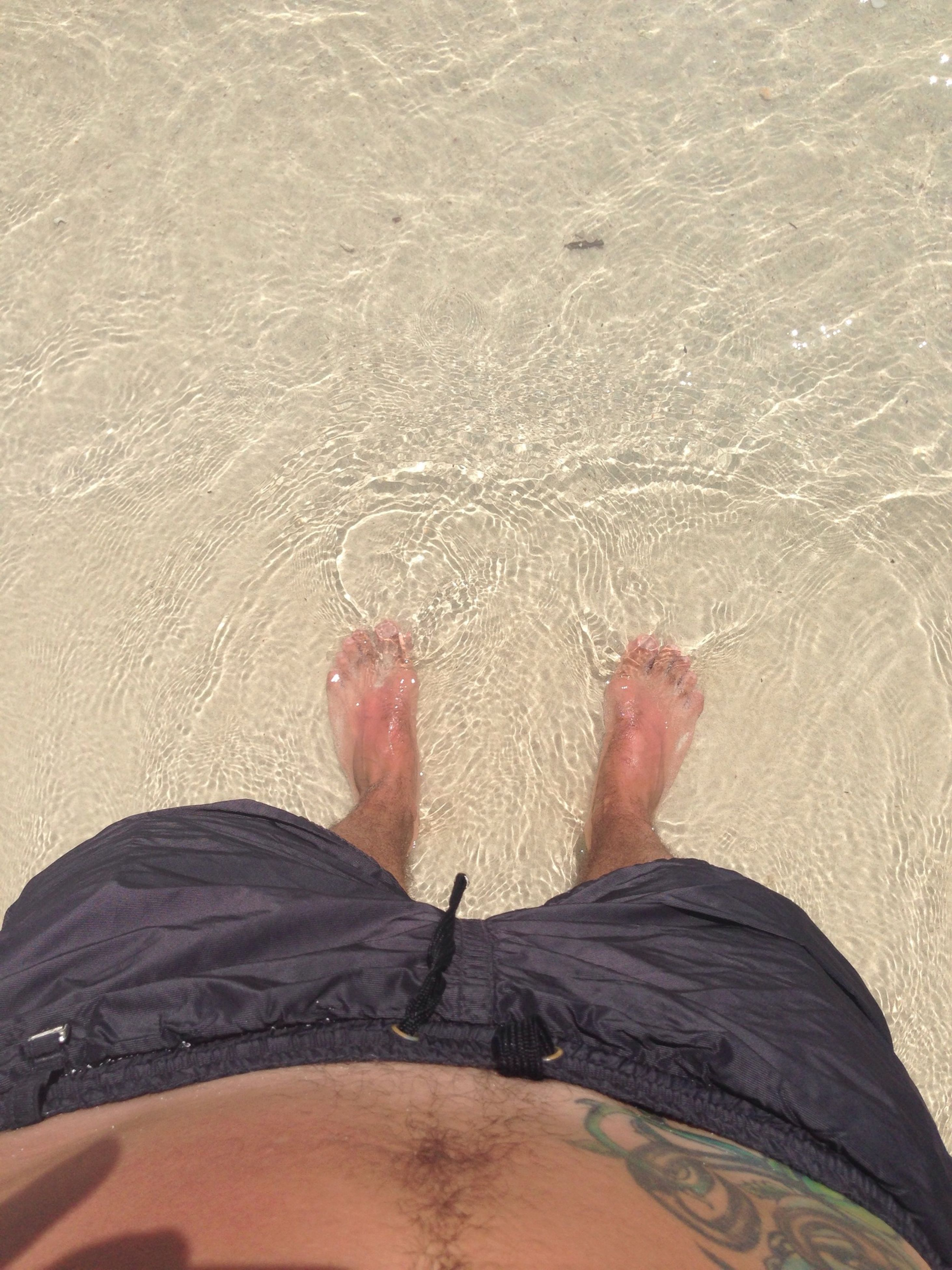 low section, person, personal perspective, lifestyles, leisure activity, barefoot, beach, sand, human foot, water, high angle view, men, part of, sunlight, unrecognizable person, standing