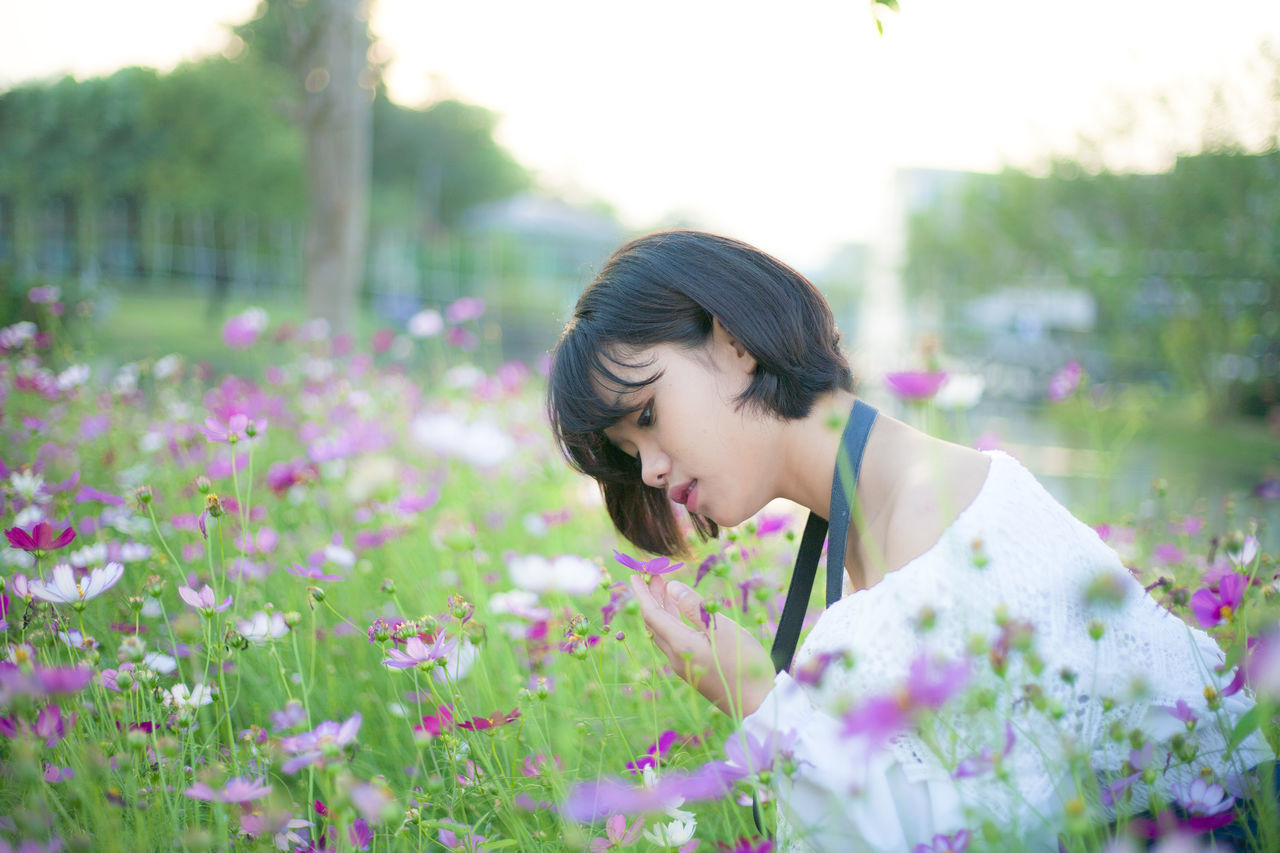 flower, black hair, one person, young adult, day, growth, fragility, outdoors, nature, young women, plant, real people, beauty in nature, lifestyles, beautiful woman, eyeglasses, tree, freshness, flower head, adult, people