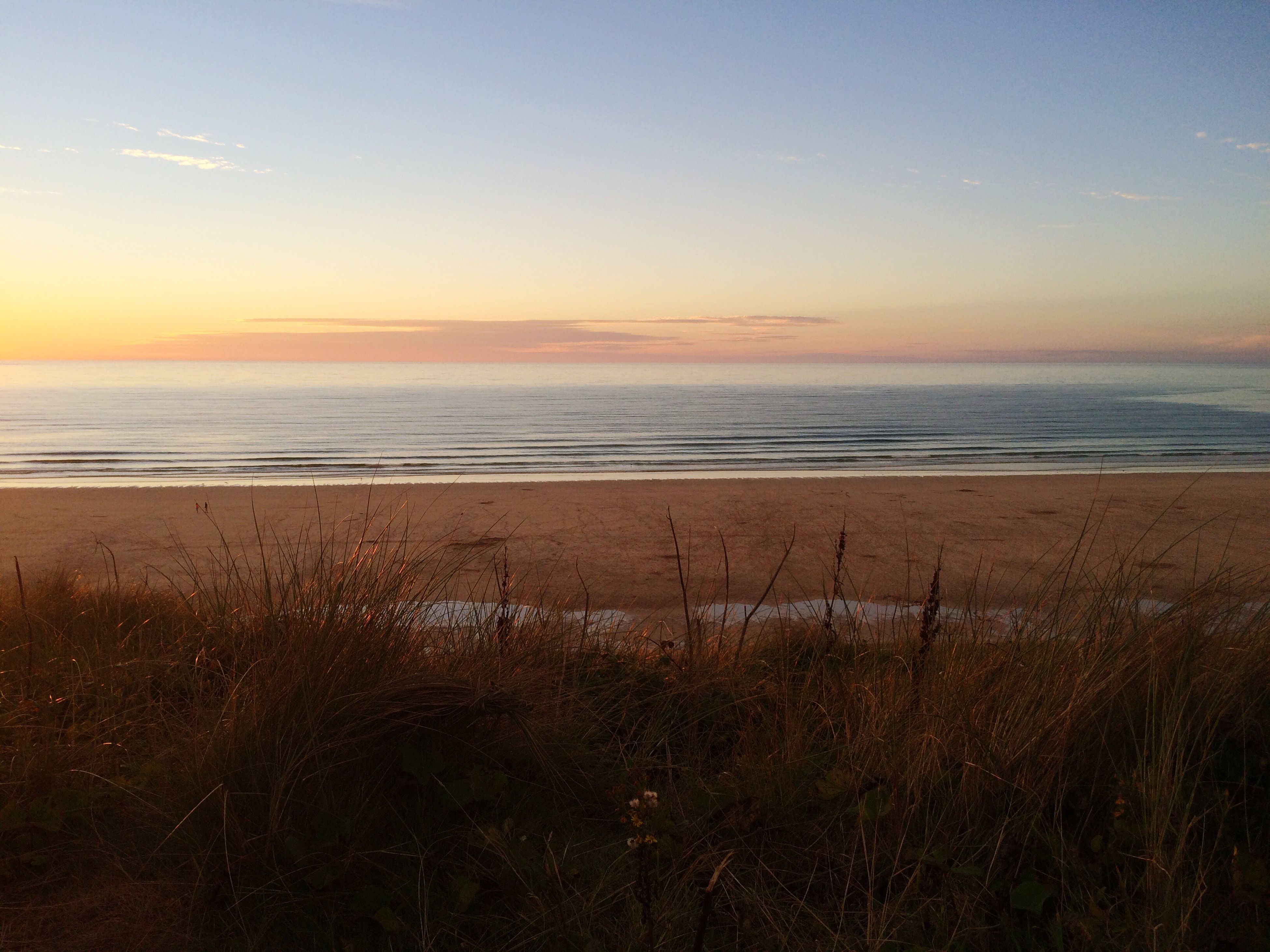 beach, water, sunset, grass, scenics, sand, shore, sea, tranquility, tranquil scene, beauty in nature, horizon over water, idyllic, sky, nature, plant, cloud, non-urban scene, calm, coastline, growth, majestic, blue, wave, dawn, orange color, sunrise - dawn, seascape, remote, outdoors, vacations, sunrise, no people, green color, ocean
