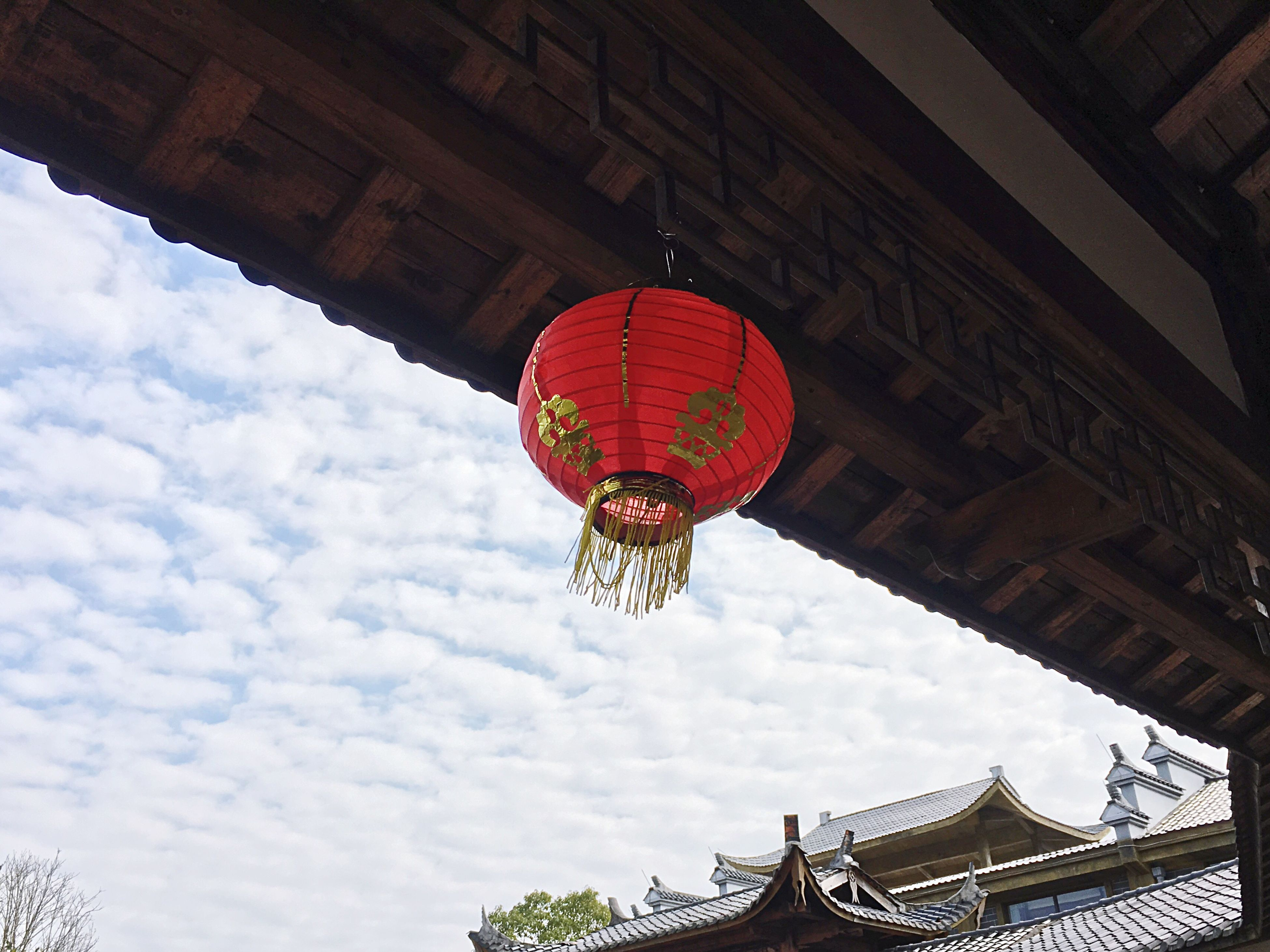 low angle view, chinese lantern, hanging, lantern, cultures, chinese lantern festival, chinese new year, built structure, celebration, sky, building exterior, architecture, red, outdoors, traditional festival, lighting equipment, city, no people, cloud - sky, day