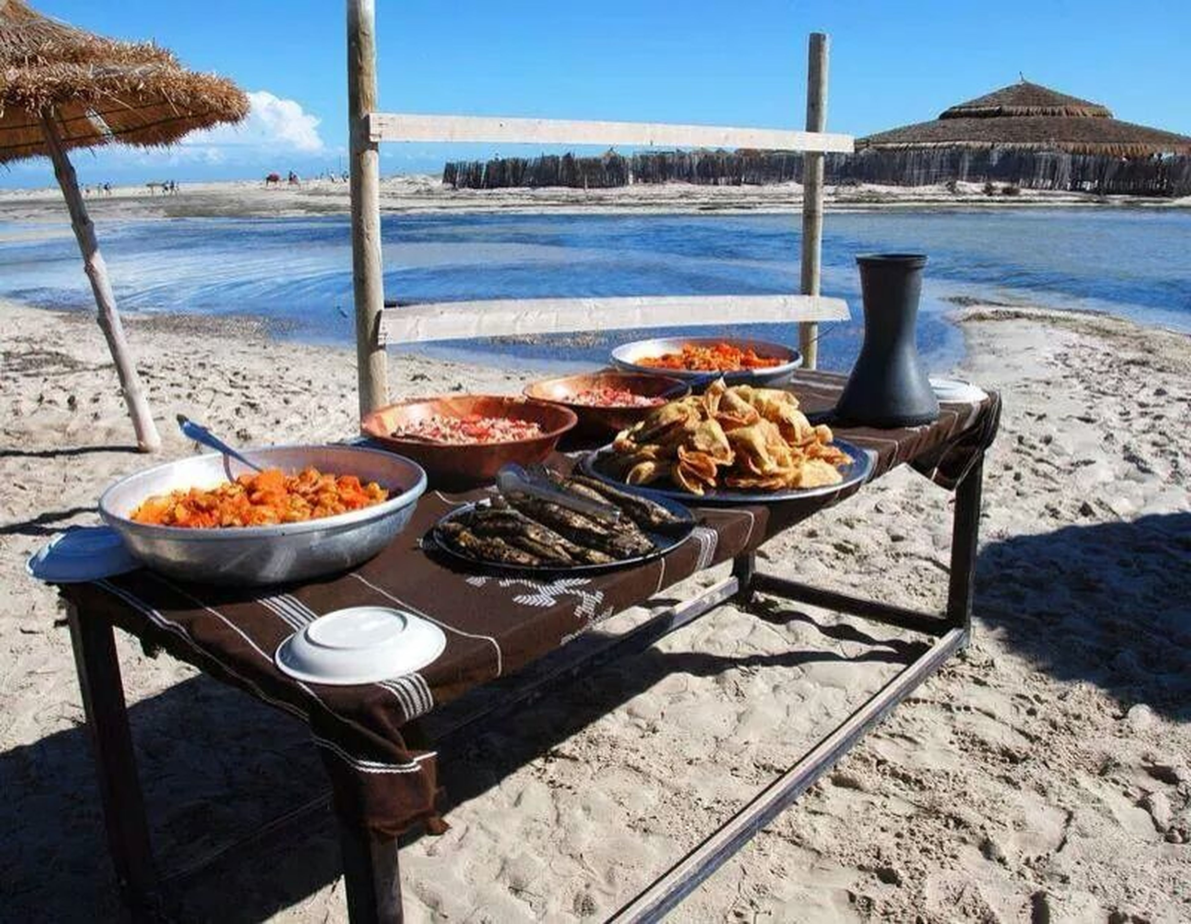 sea, table, beach, sunlight, food and drink, chair, water, shadow, clear sky, shore, day, food, outdoors, sunny, absence, sky, wood - material, railing, restaurant, nature
