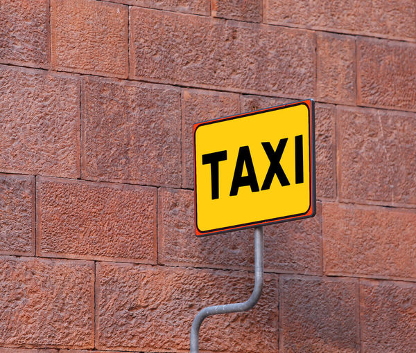yellow TAXI sign on the taxi stop with a wall of an old building Indications Milano Rome Sign Stopping Taxi Taxi Driver Taxi Stop Transportation Banner Brick Wall Communication Florence No People Outdoors Road Sign Road Signal Roadsign Stop Stop Taxi Yellow