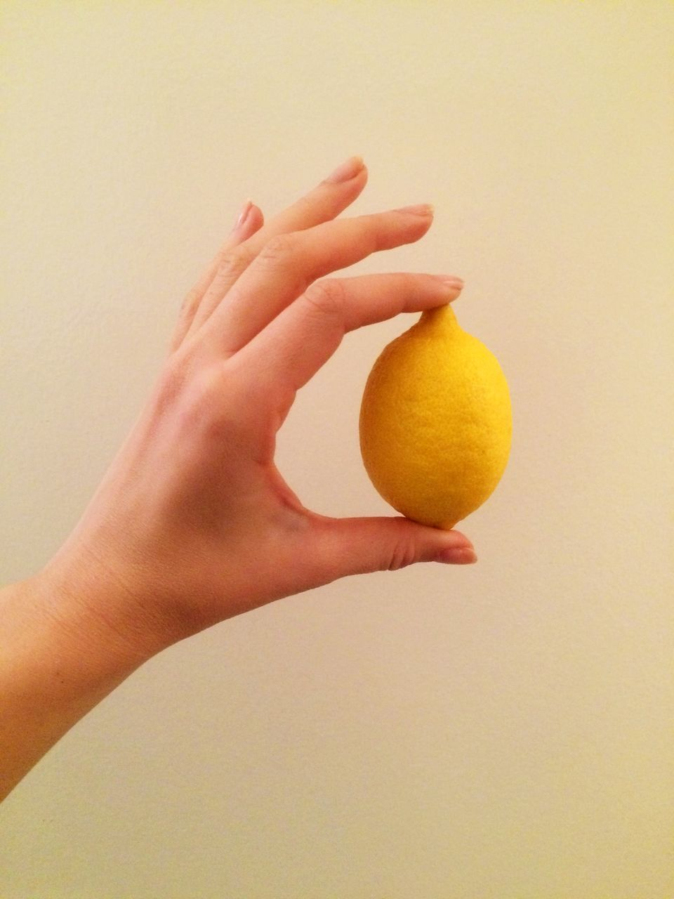 Cropped Hand Of Woman Holding Lemon Against Beige Background