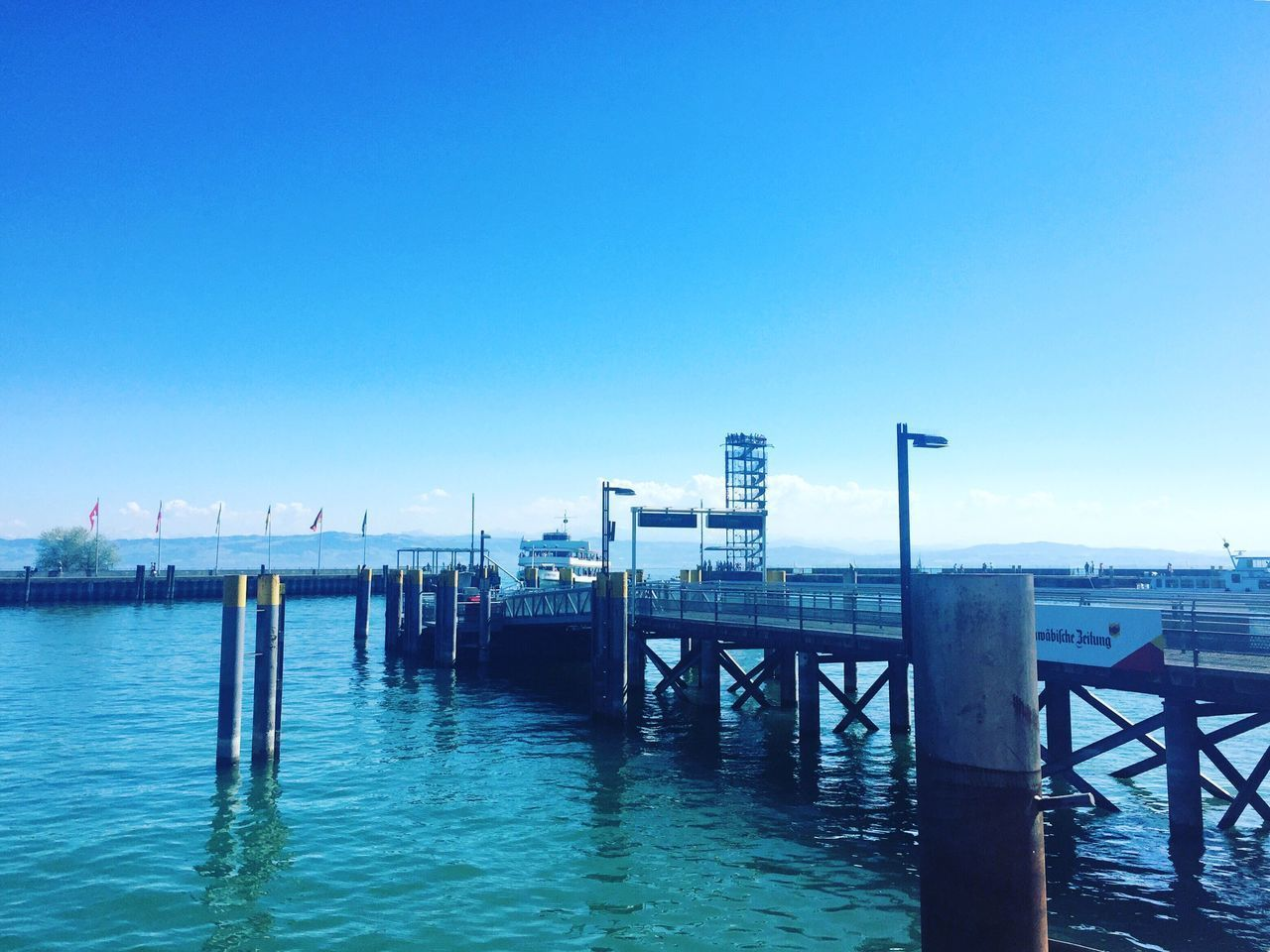 blue, water, pier, outdoors, day, built structure, wooden post, tranquility, nature, architecture, sky, sea, clear sky, no people, scenics, beauty in nature