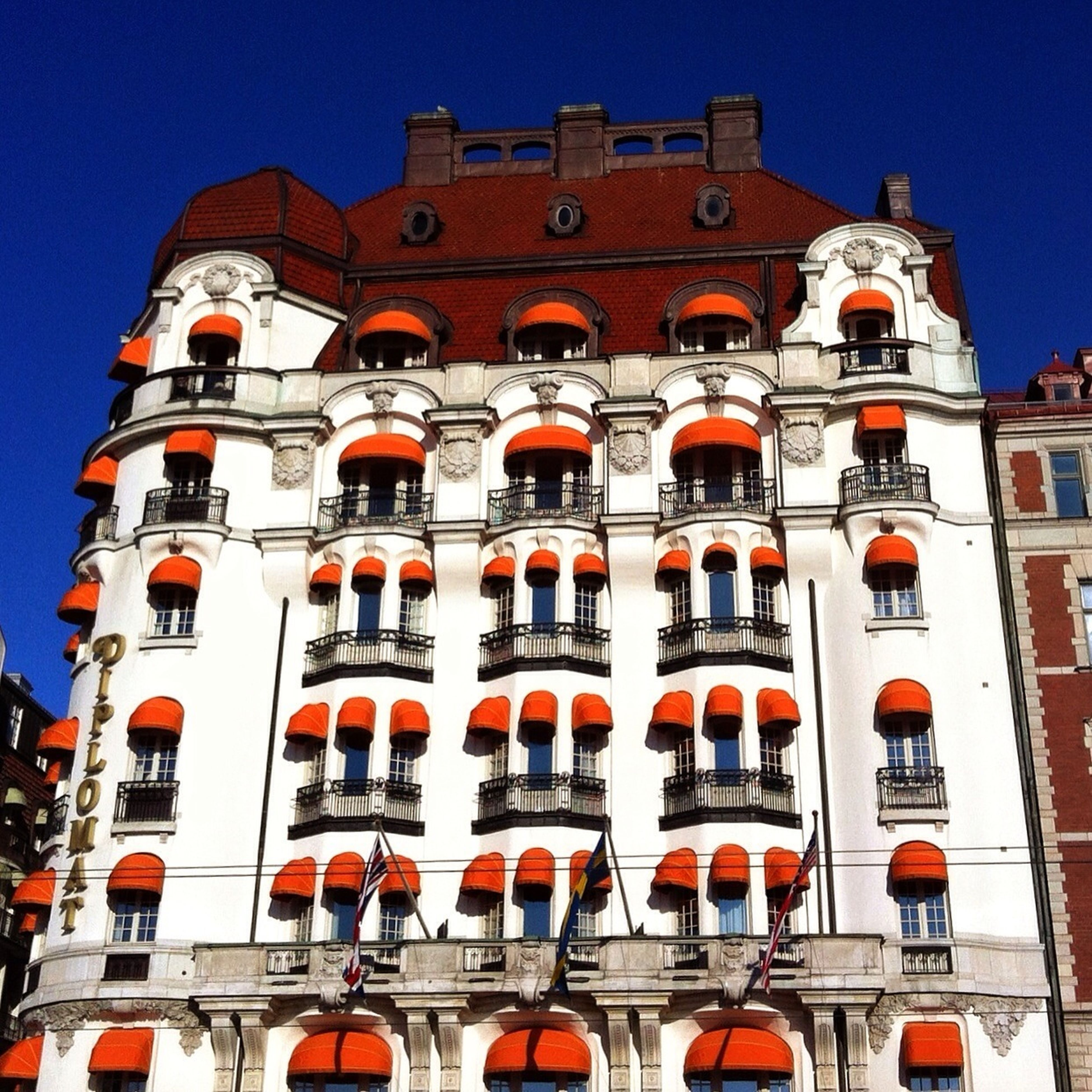 architecture, building exterior, built structure, low angle view, window, clear sky, arch, blue, facade, building, sunlight, outdoors, day, exterior, residential building, residential structure, no people, history, city, balcony