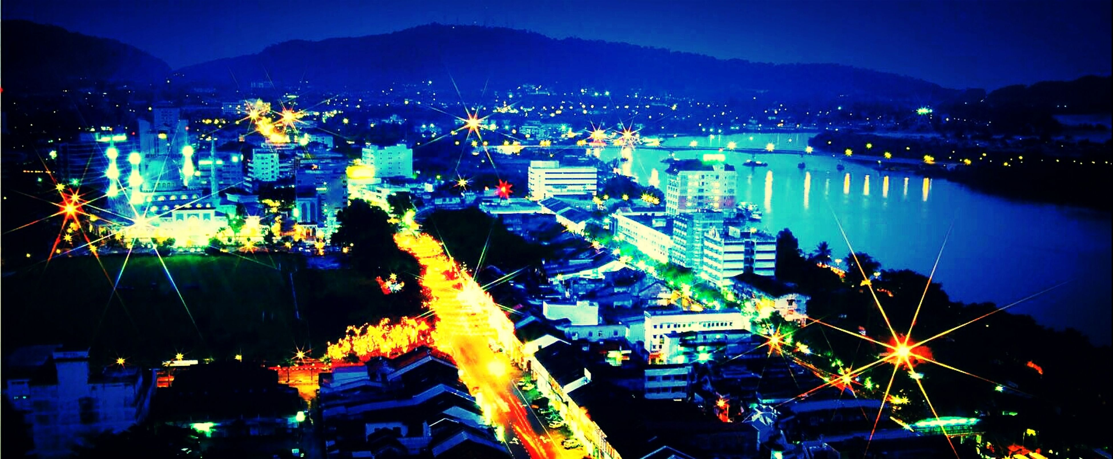 illuminated, night, city, cityscape, building exterior, architecture, built structure, high angle view, mountain, sky, crowded, residential district, city life, river, blue, water, residential building, outdoors, dusk, clear sky
