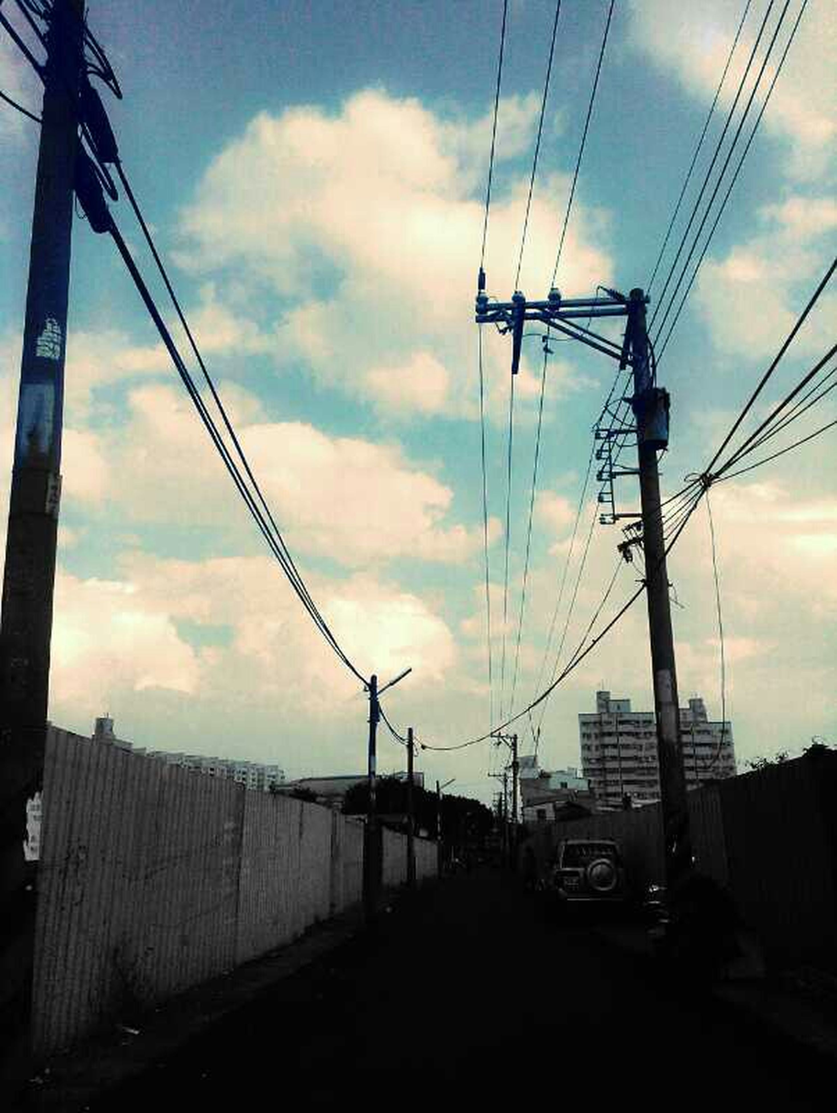 power line, electricity pylon, sky, cable, power supply, electricity, built structure, architecture, connection, cloud - sky, low angle view, building exterior, fuel and power generation, cloudy, silhouette, power cable, cloud, technology, transportation, sunset
