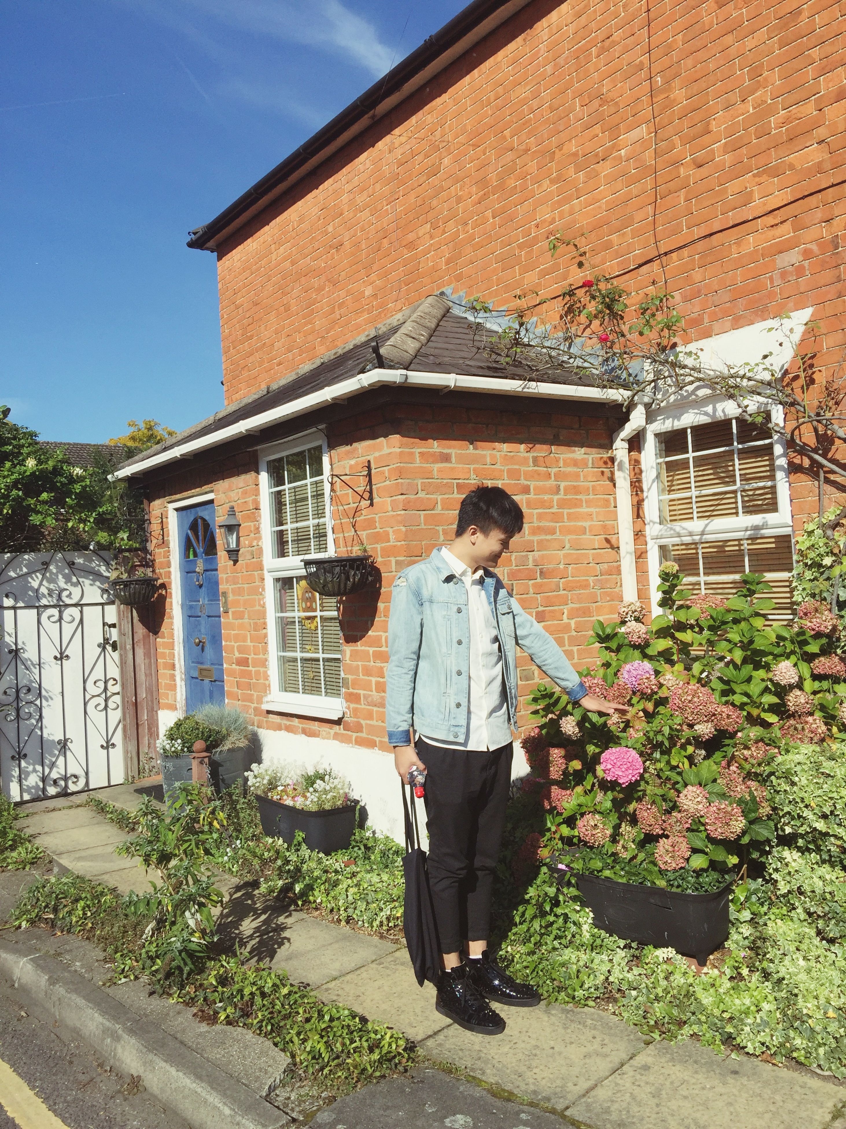 building exterior, architecture, built structure, casual clothing, lifestyles, full length, young adult, leisure activity, person, house, standing, young women, residential structure, plant, rear view, sunlight, three quarter length, sky