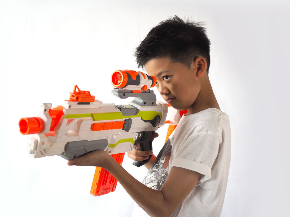 Boys Casual Clothing Childhood Close-up Concentration Day Education Elementary Age Holding Indoors  Learning Leisure Activity Lifestyles Model - Object One Boy Only One Person People Playing Real People Standing Studio Shot Asian Boy Toy Guns