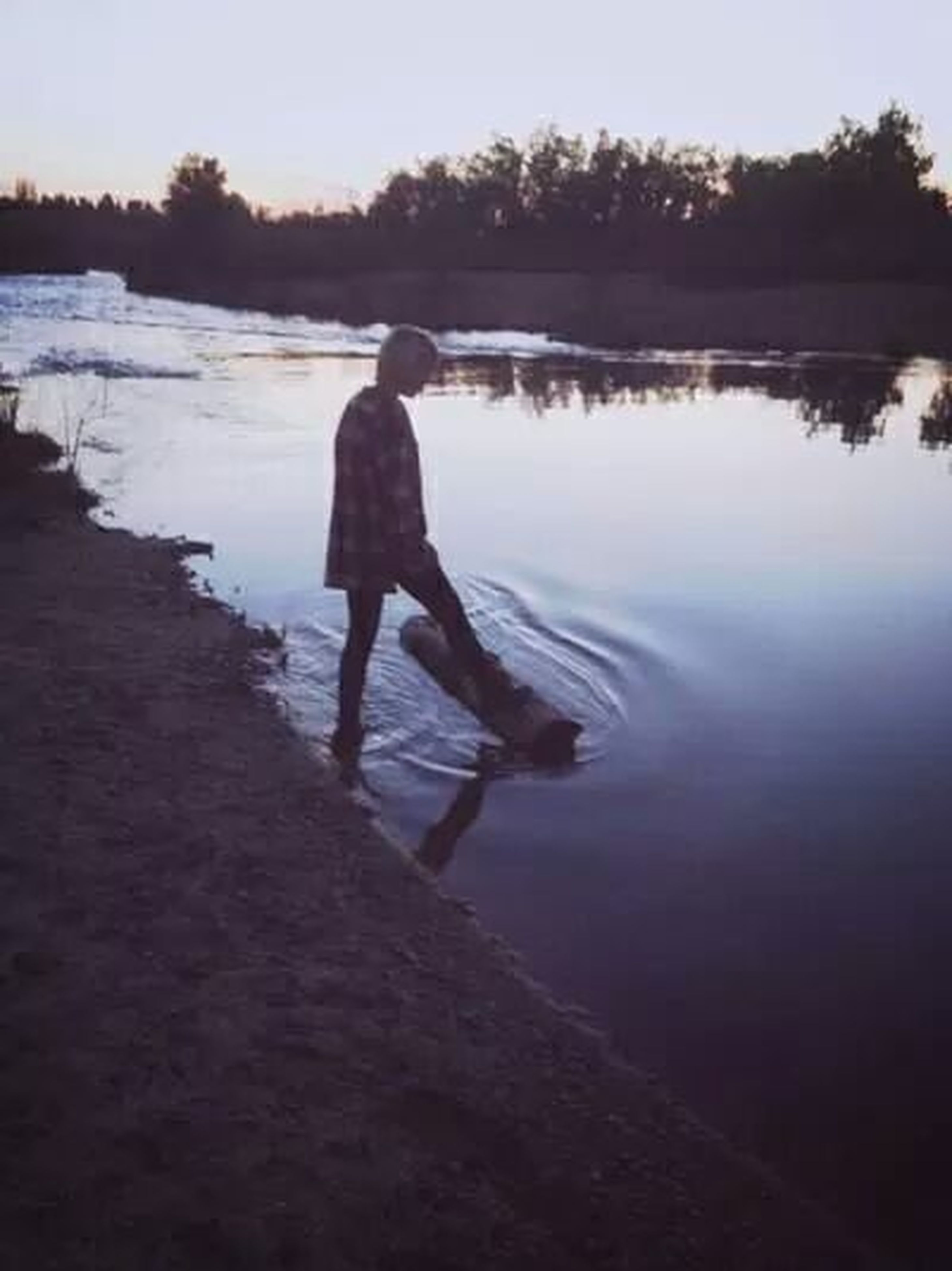 full length, water, lifestyles, leisure activity, rear view, standing, lake, tranquility, silhouette, tranquil scene, reflection, nature, scenics, sky, beauty in nature, casual clothing, walking, sunset
