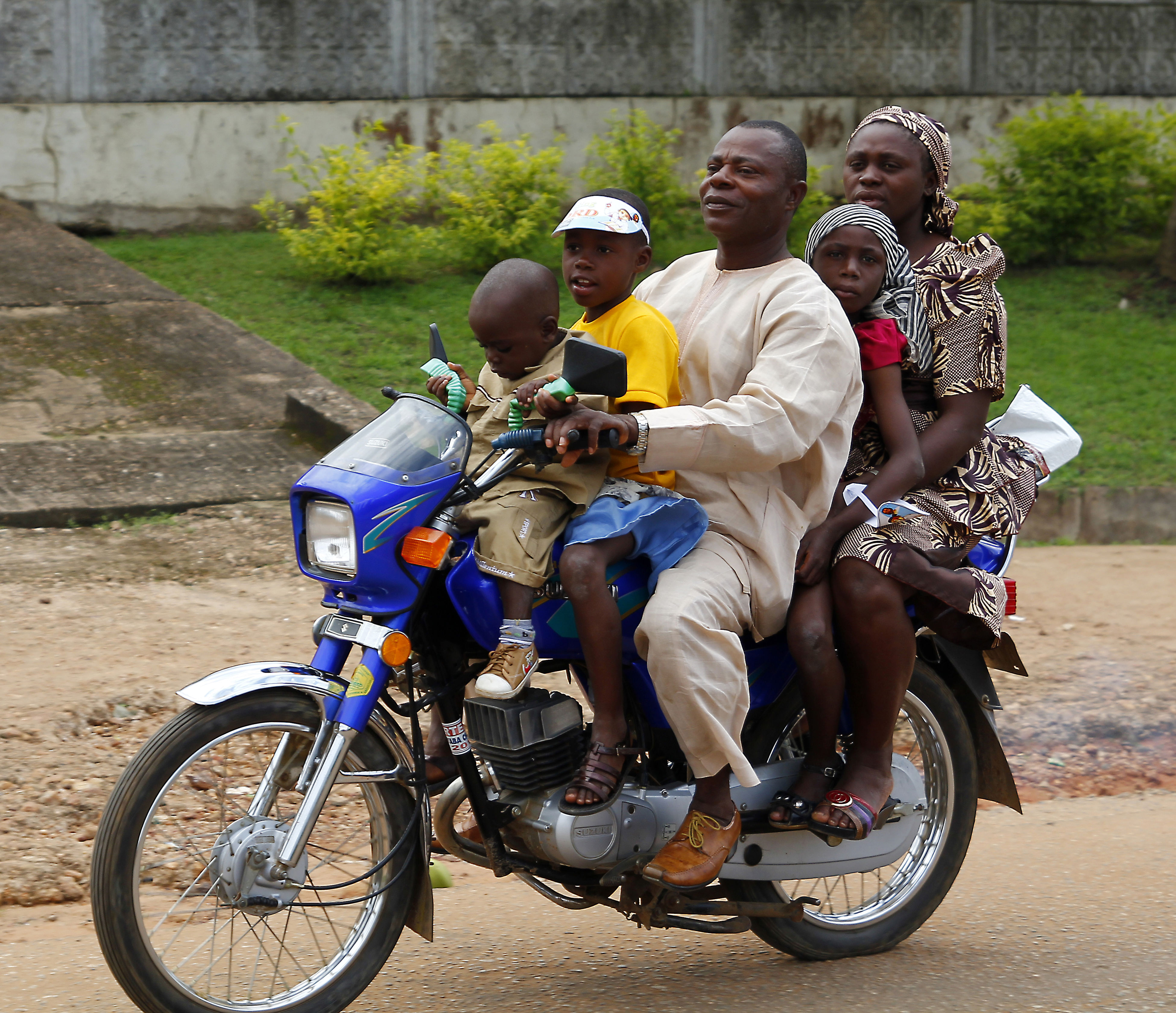 Five members of a nigerian family travelling by motorcycle, in the city of Akure, in the south-west of Nigeria. Akure Akure, Alone Balance Childhood Daughter Day Five Friendship Front View Fun Land Vehicle Lifestyles Mode Of Transport Motor Scooter Motorcycle Nigeria Parking Real People Side View Sitting Son Transportation First Eyeem Photo