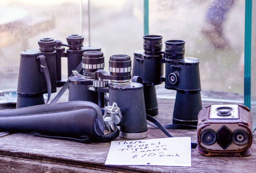 old binoculars and an old camera aare for sale at an area antique shop Horizontal Retro Sale Seeing the Sights Antiques Binoculars Black Close-up Day Distance Indoors  No People Old Camera Old Technology' Old-fashioned Technology Tools