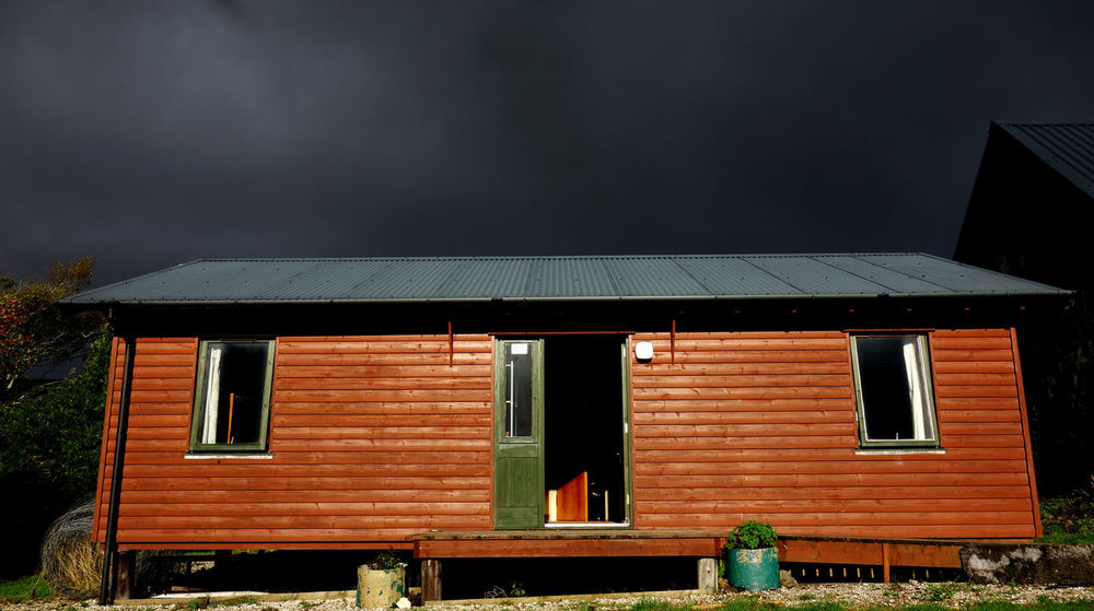 I had the honor to stay in this cozy hide-away at Flora McDonald's on the Isle of Skye. A very peaceful and quiet place on with a very friendly owner. In the morning there were these dark rainy clouds in the sky and at the same time a very intense warm sunlight from behind. Architecture Cabin Light And Shadow Clouds Country House Outdoors Country Life Countryside The Architect - 2016 EyeEm Awards Hideaway Minimalism Cozy House Scotland Secret Hideaway Travel Home Home Sweet Home Travel Photography Traveling Travelling Travelphotography Homesweethome Window Windows