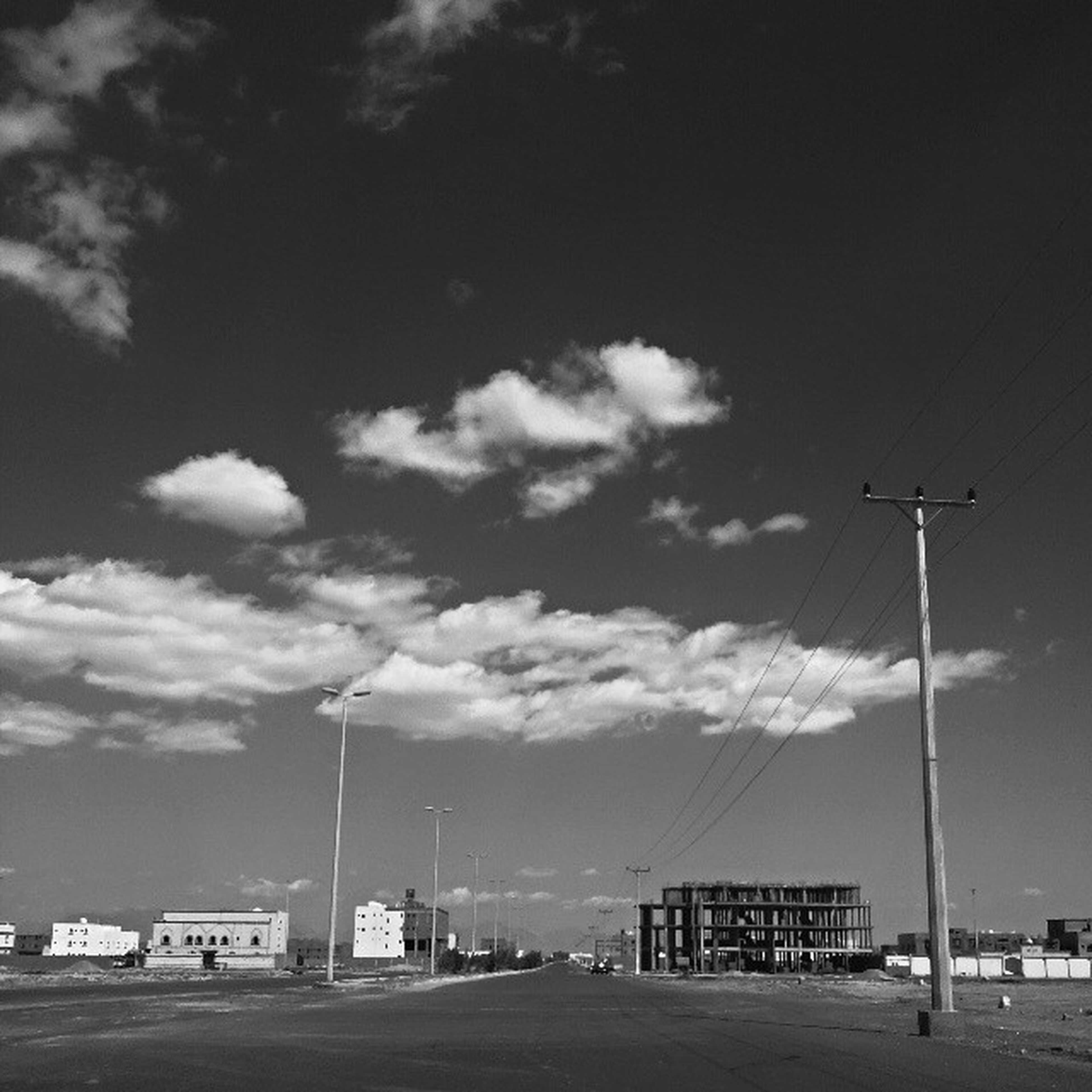 sky, transportation, street light, car, mode of transport, cloud - sky, road, street, cloud, low angle view, land vehicle, electricity pylon, pole, electricity, power line, day, cloudy, outdoors, no people, fuel and power generation