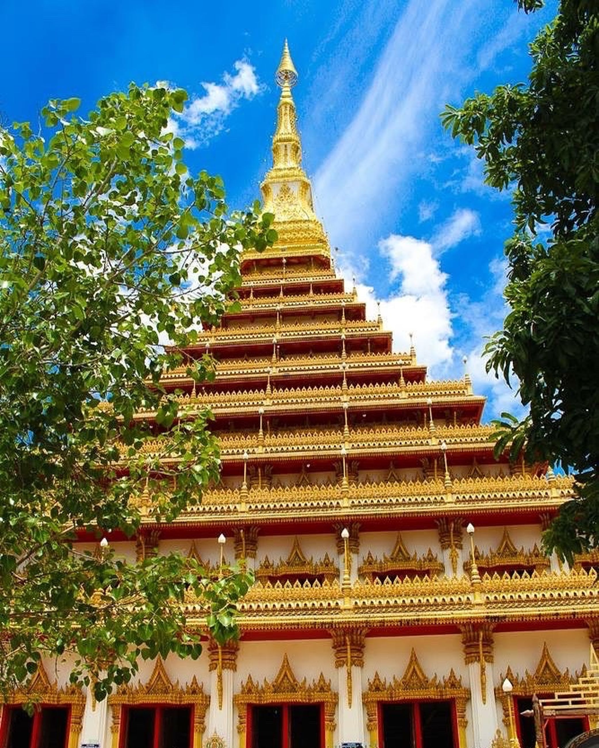 architecture, built structure, building exterior, tree, spirituality, religion, place of worship, low angle view, temple - building, sky, pagoda, day, spire, tourism, outdoors, tall, tall - high, majestic, temple, no people, stupa