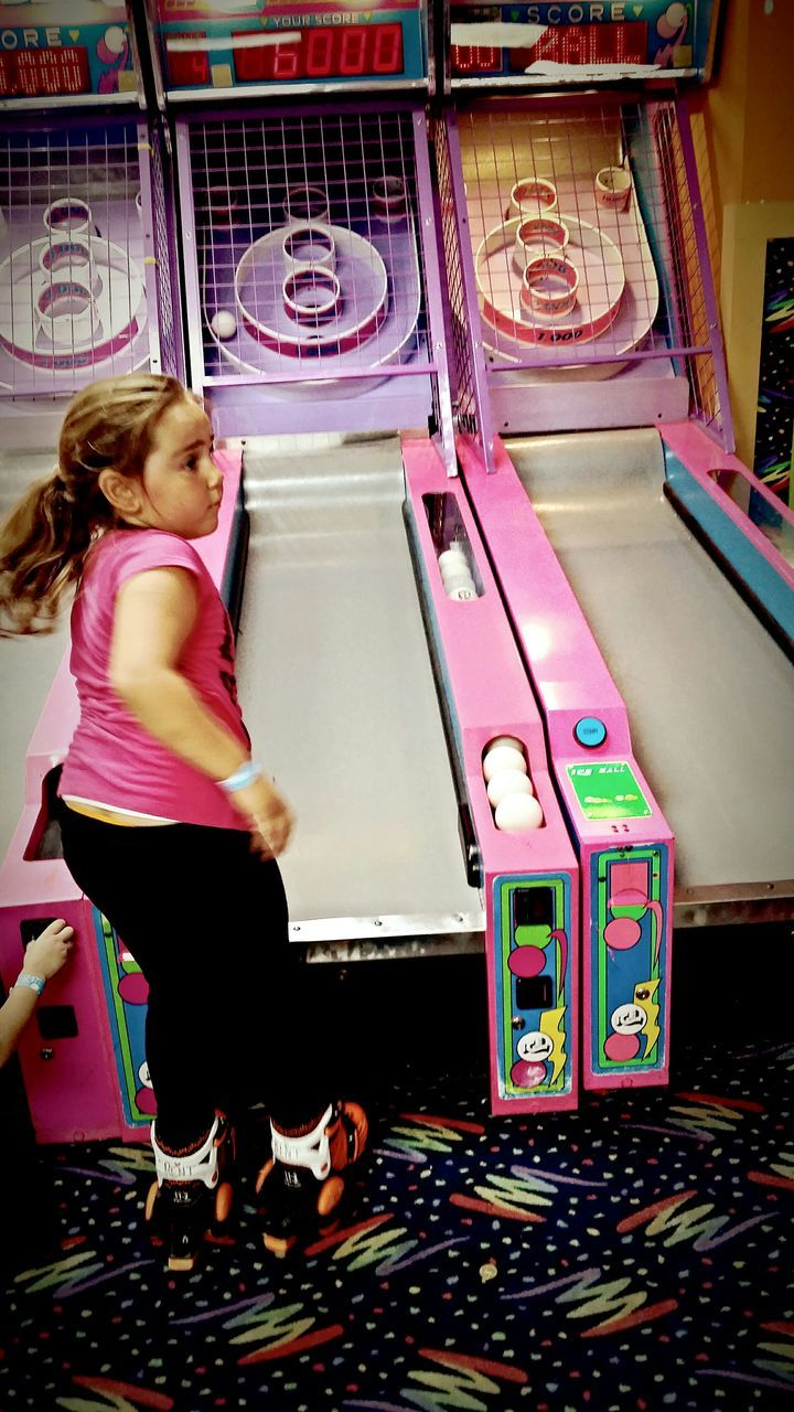 full length, leisure activity, lifestyles, one person, childhood, playing, real people, girls, indoors, casual clothing, slot machine, standing, gambling, choice, young adult, day, people