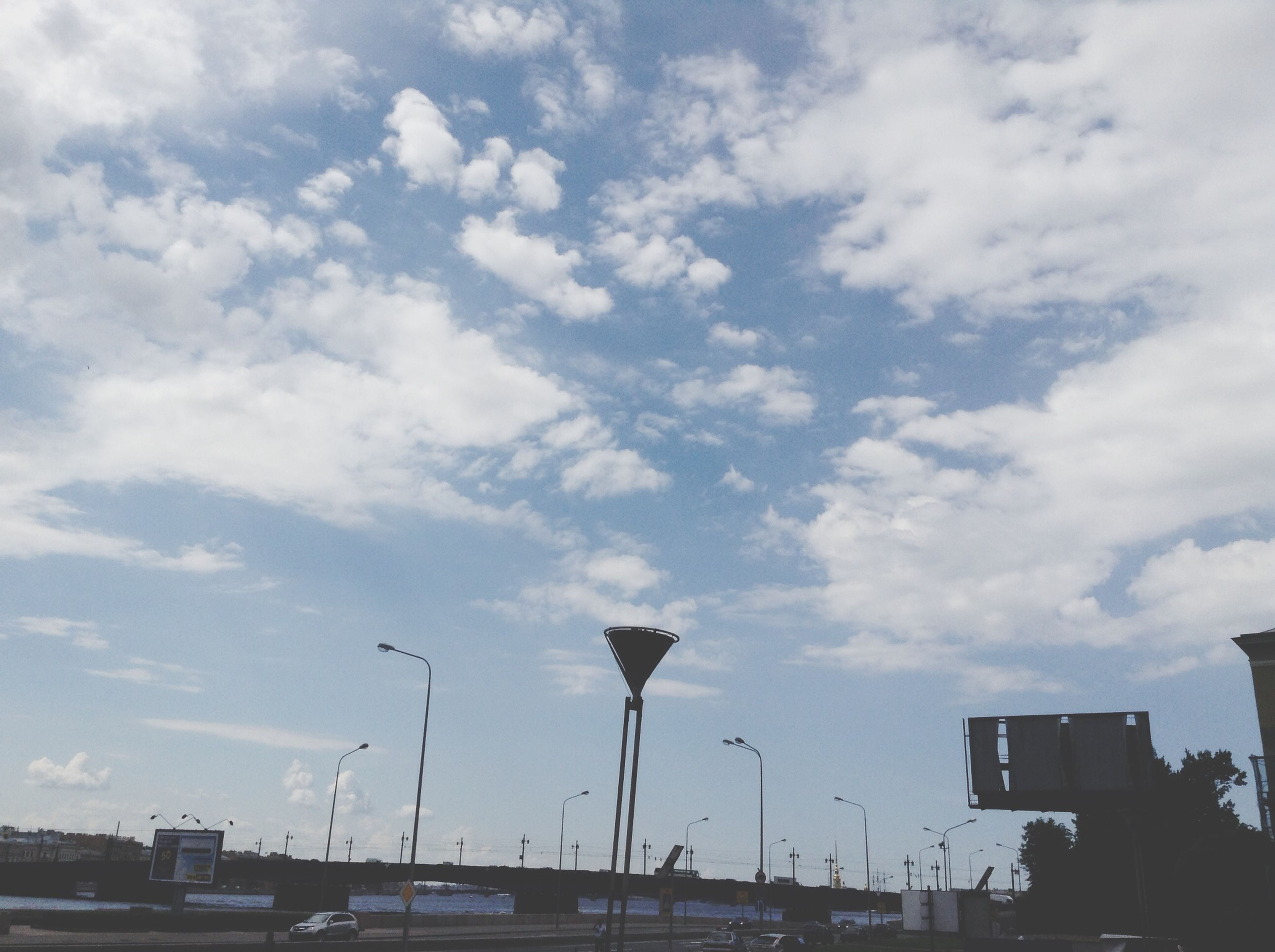 sky, cloud - sky, low angle view, cloudy, building exterior, built structure, cloud, architecture, flying, transportation, day, outdoors, no people, city, nature, mode of transport, weather, bird, building, overcast