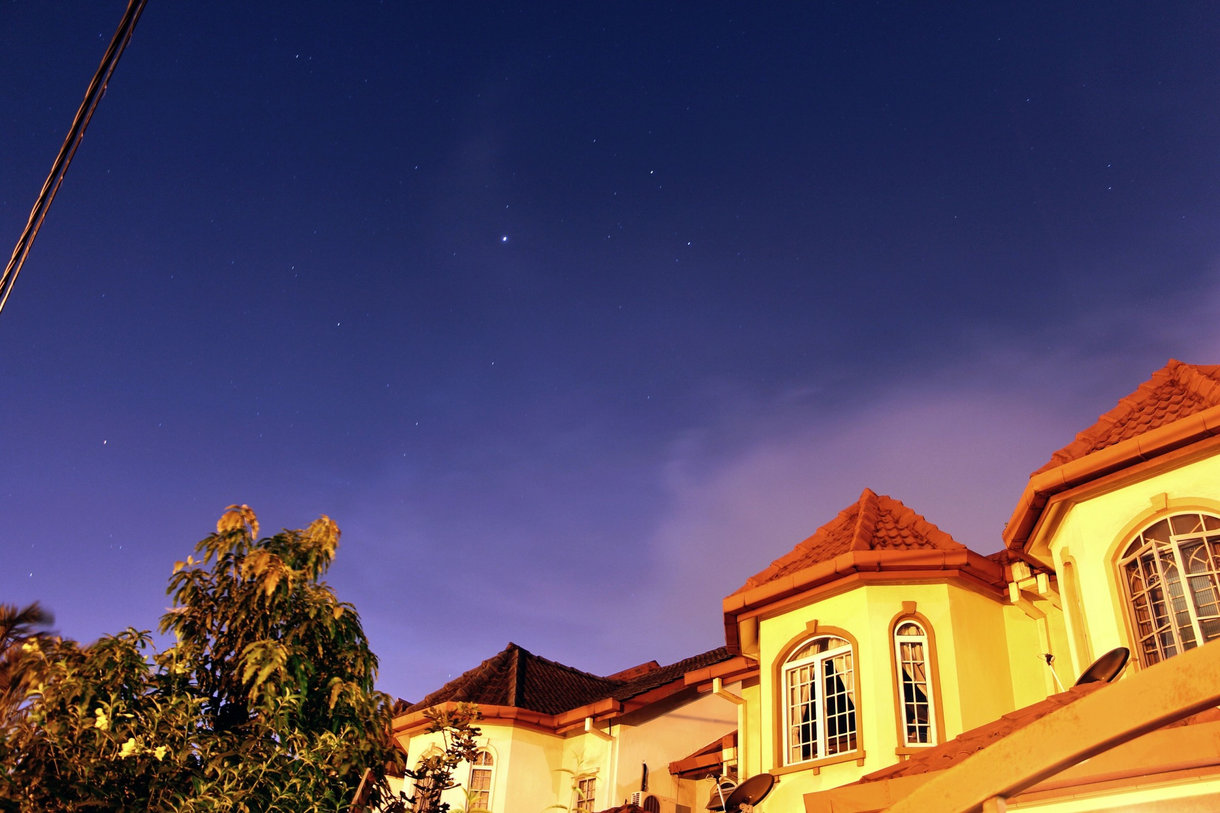 building exterior, architecture, built structure, low angle view, house, night, sky, blue, residential structure, tree, residential building, high section, moon, illuminated, outdoors, building, clear sky, window, street light, no people