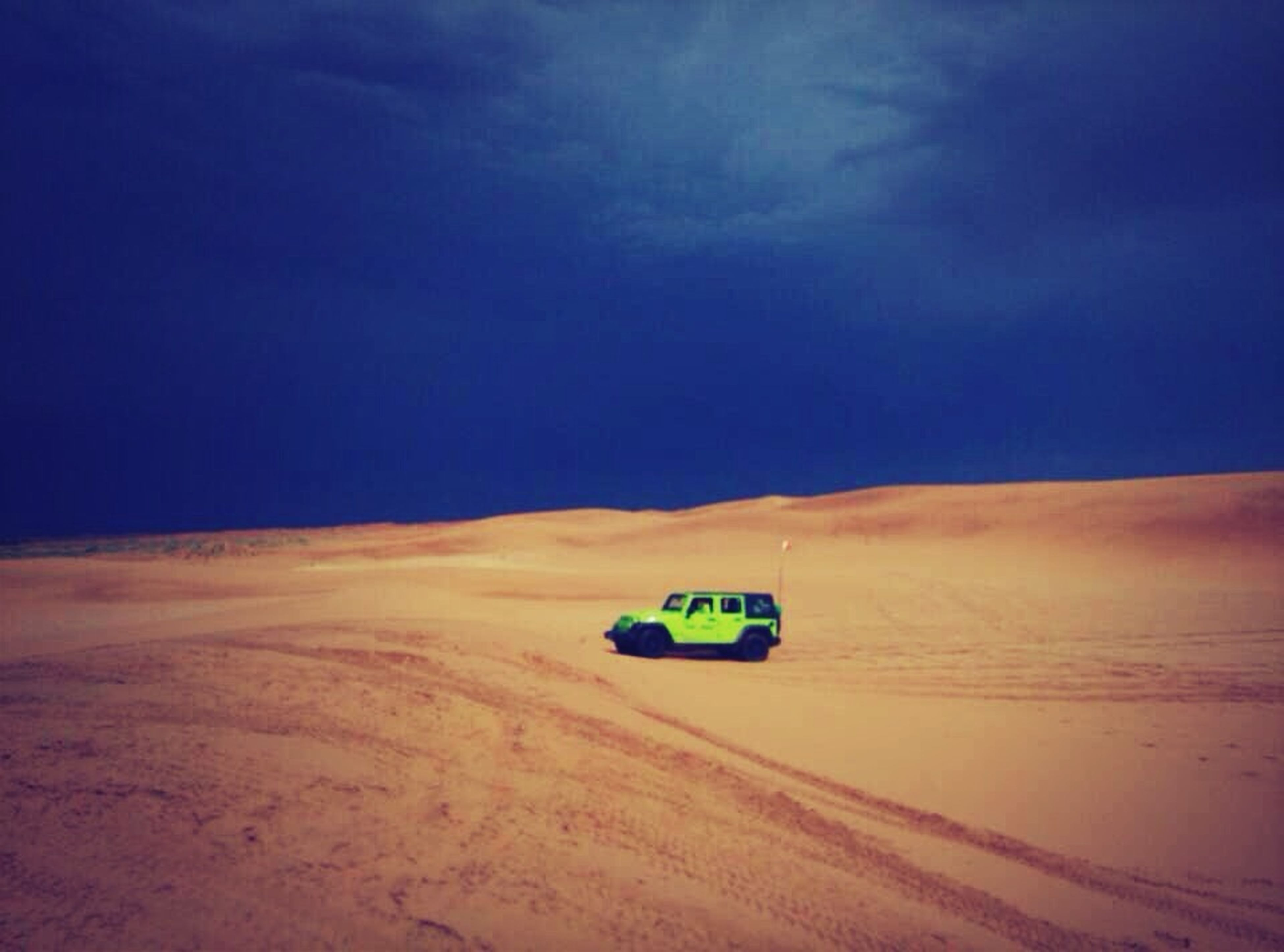 transportation, sand, sky, blue, landscape, tranquility, land vehicle, tranquil scene, desert, nature, scenics, sunlight, outdoors, mode of transport, road, day, beauty in nature, car, no people, non-urban scene