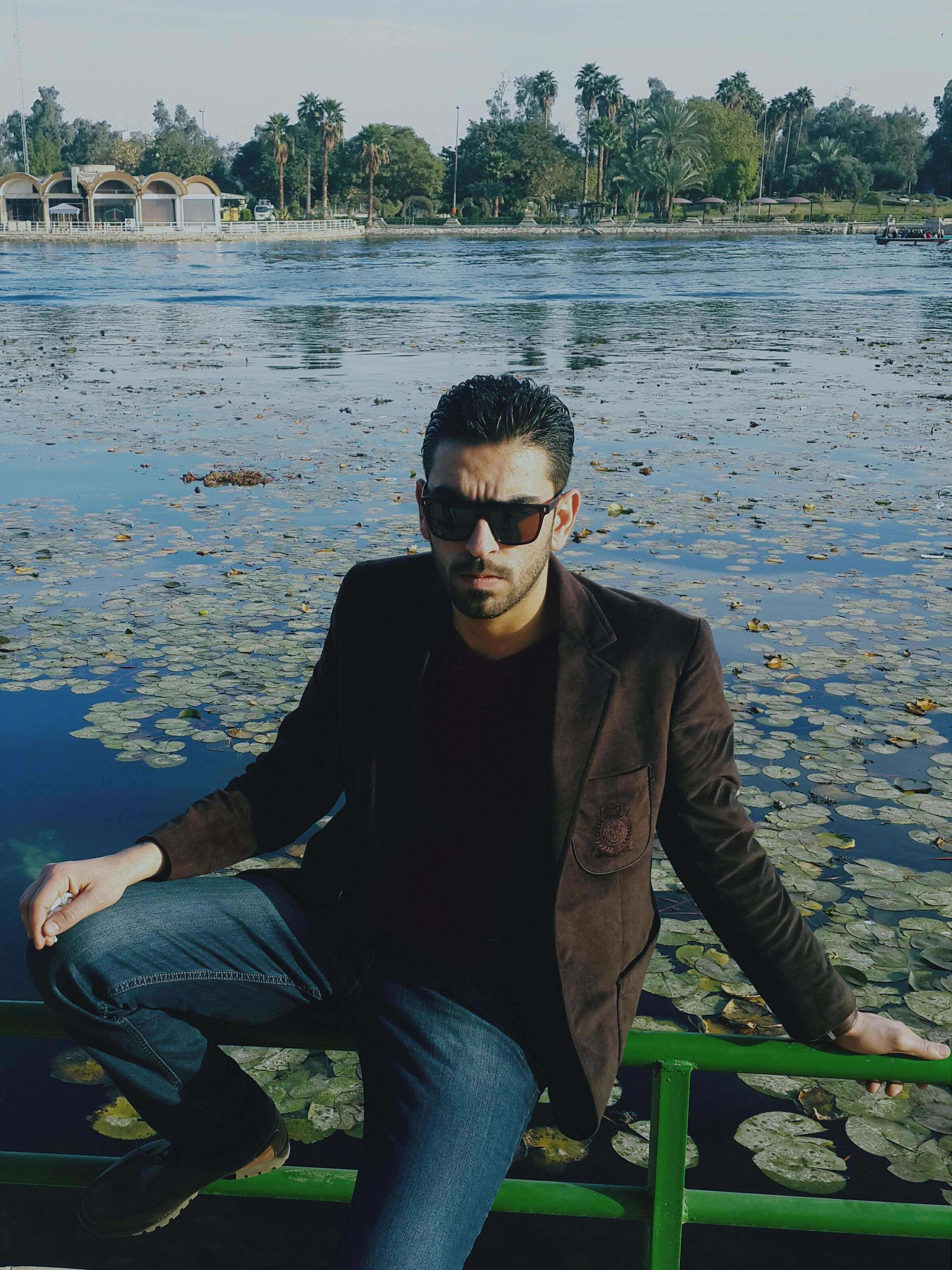 water, lifestyles, casual clothing, leisure activity, young adult, lake, portrait, person, standing, looking at camera, sunglasses, three quarter length, sitting, river, waist up, young men, front view