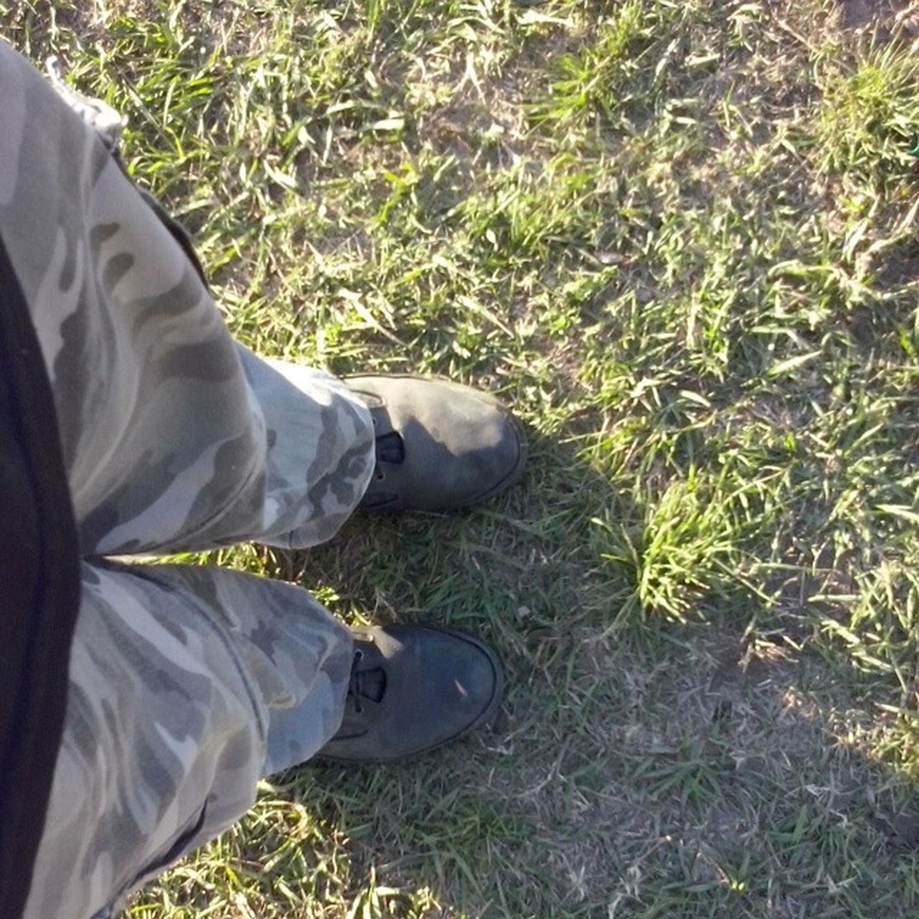 low section, shoe, person, jeans, grass, footwear, lifestyles, high angle view, personal perspective, standing, field, men, leisure activity, human foot, grassy, casual clothing, canvas shoe