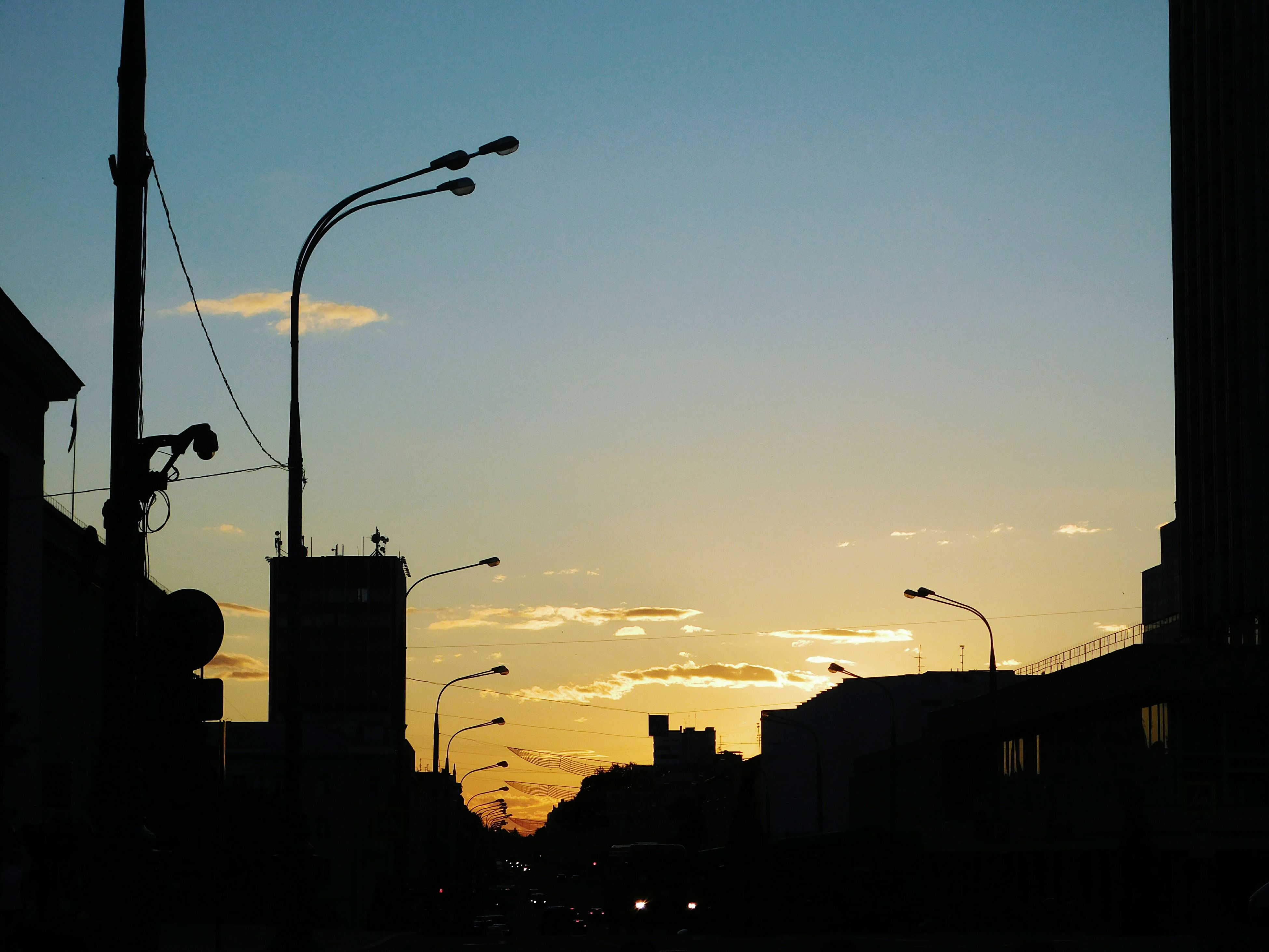 sunset, silhouette, architecture, built structure, building exterior, street light, no people, city, sky, outdoors, nature, clear sky, beauty in nature, bird, cityscape