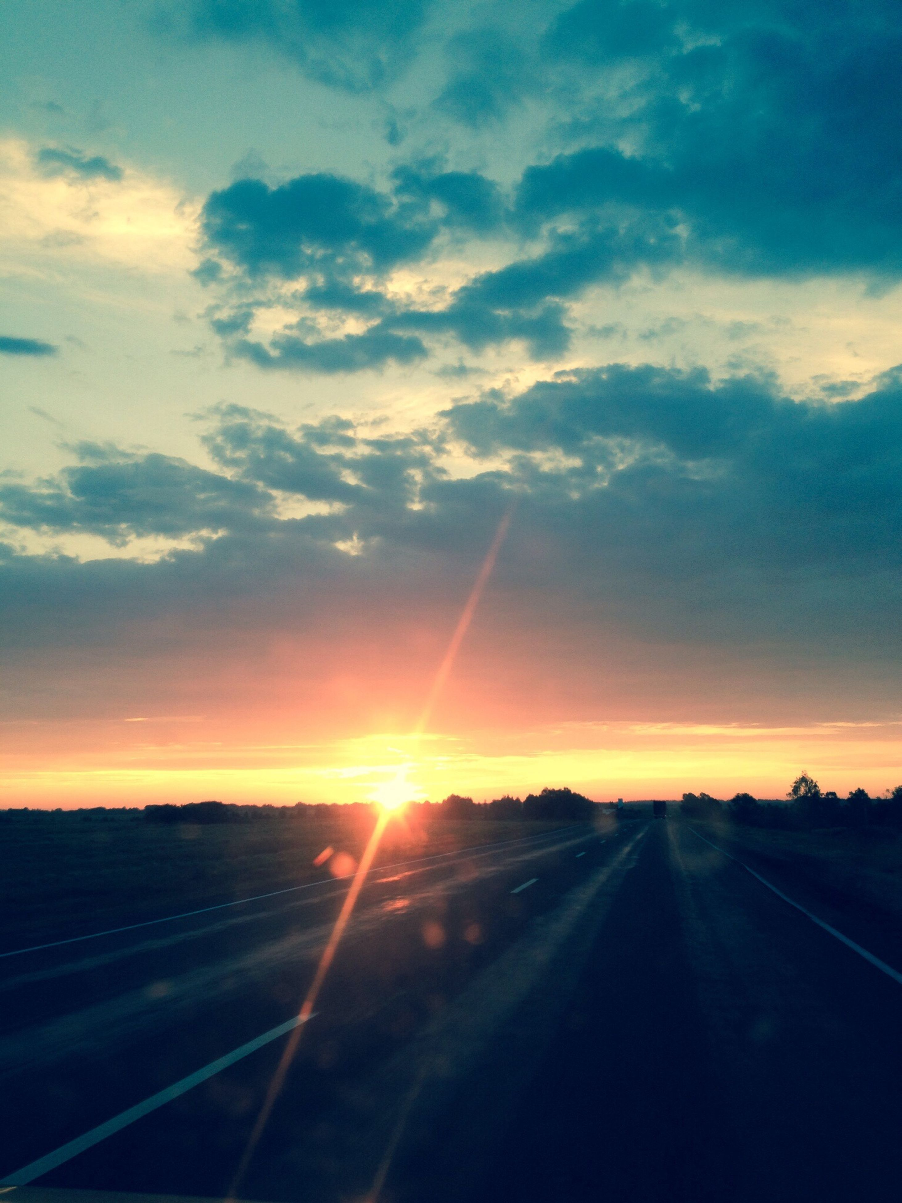sunset, road, transportation, sky, the way forward, sun, landscape, tranquil scene, scenics, tranquility, diminishing perspective, cloud - sky, country road, beauty in nature, sunbeam, sunlight, nature, vanishing point, cloud, orange color