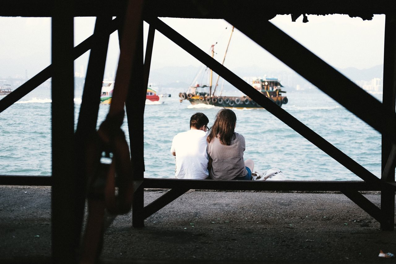 Rear View Of Couple Sitting By Harbor