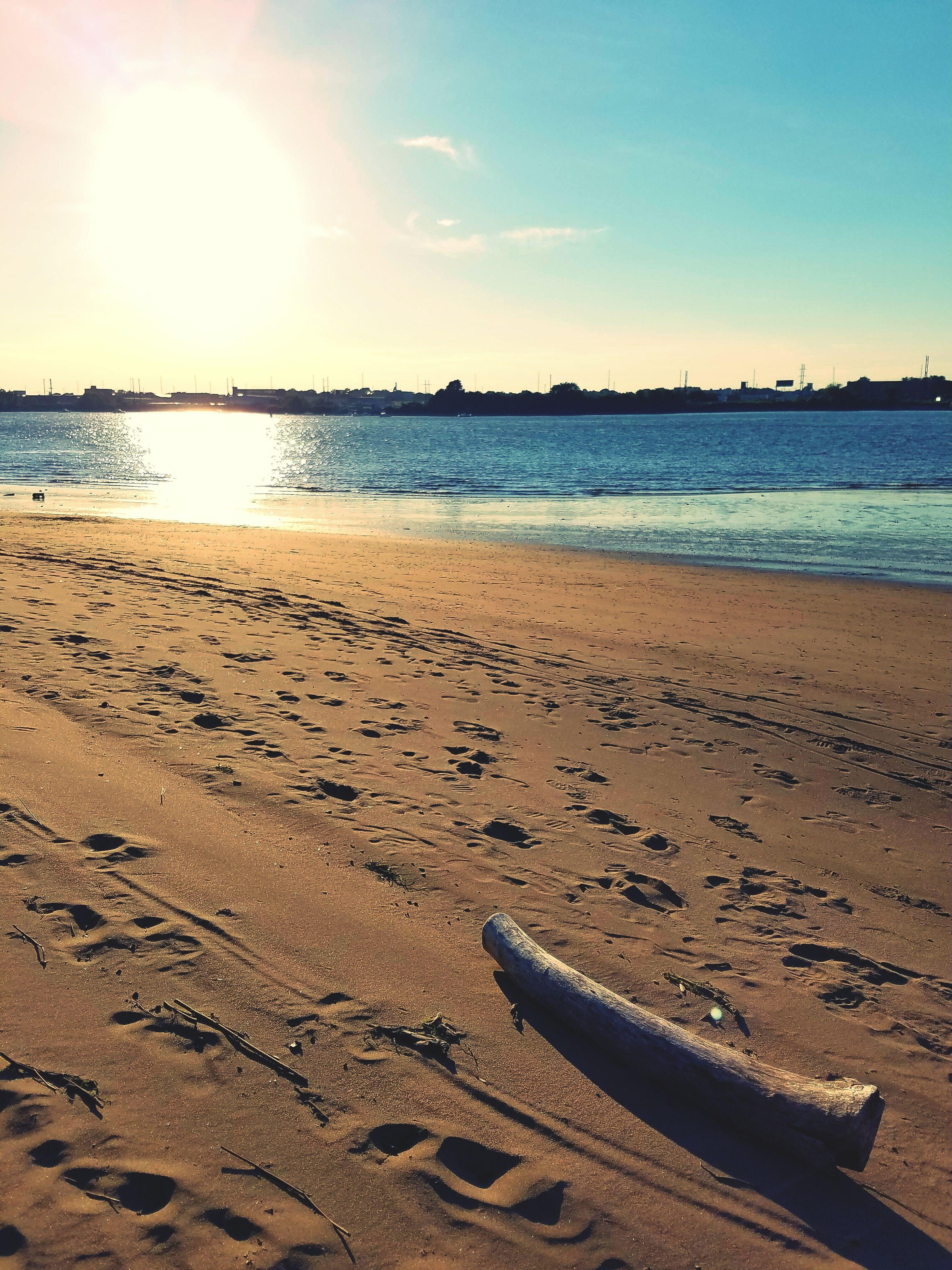 beach, sand, water, sea, shore, sunlight, tranquility, tranquil scene, sky, scenics, nature, beauty in nature, coastline, idyllic, outdoors, sun, travel destinations, no people, sunny, non-urban scene, remote, day, sunbeam, tourism