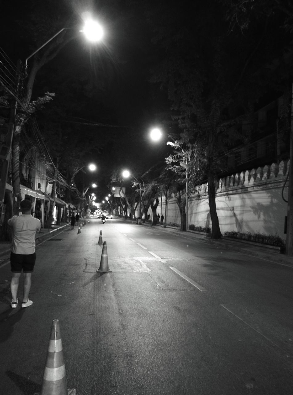 Night Illuminated Street Light City One Person Only Men Outdoors Night Street Night Street Photography Black And White Road At Night Bangkok Street Street Photography Light And Shadow Light Adapted To The City