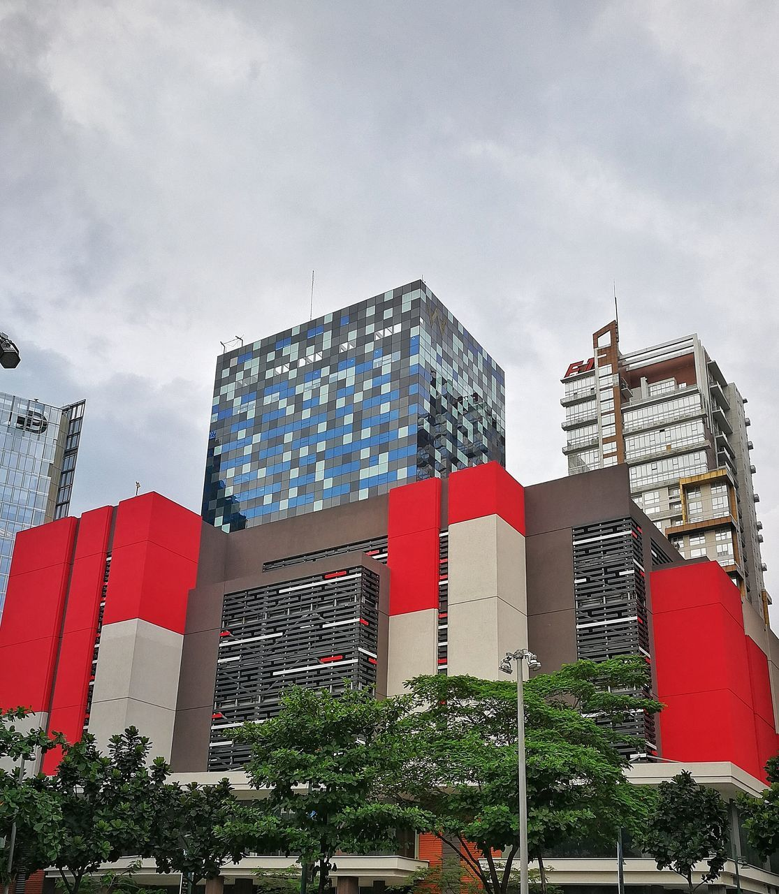architecture, building exterior, built structure, low angle view, skyscraper, modern, red, day, sky, outdoors, no people, city, tree