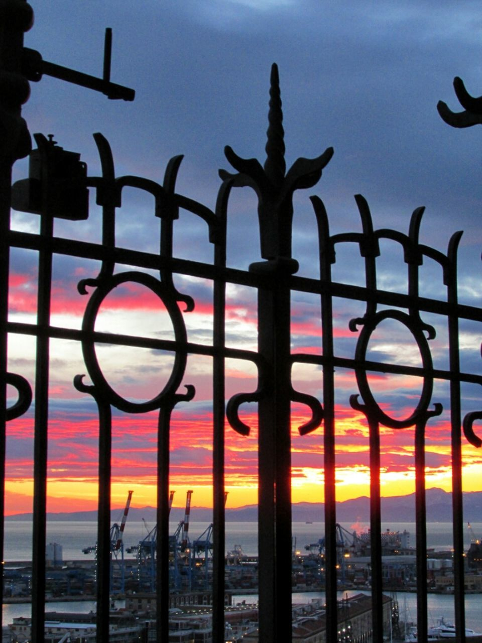 sunset, protection, silhouette, safety, dusk, metal, sky, fence, travel destinations, tranquil scene, close-up, orange color, dramatic sky, romantic sky, scenics, cloud - sky, tranquility, back lit, outdoors, atmospheric mood, atmosphere, beauty in nature, sun, nature, majestic, tourism, wide, sea