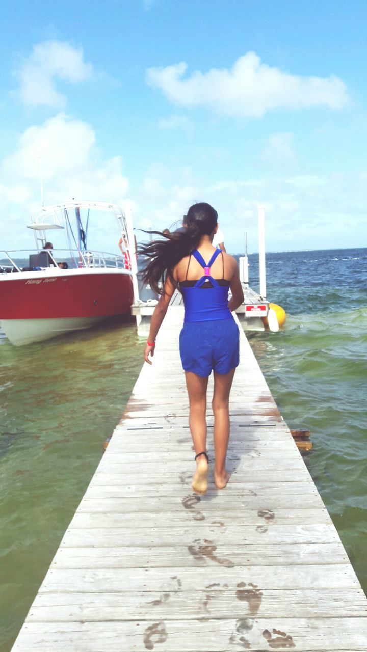 one person, sky, water, sea, full length, pier, nautical vessel, cloud - sky, day, transportation, outdoors, rear view, real people, young adult, leisure activity, standing, jetty, young women, vacations, nature, people