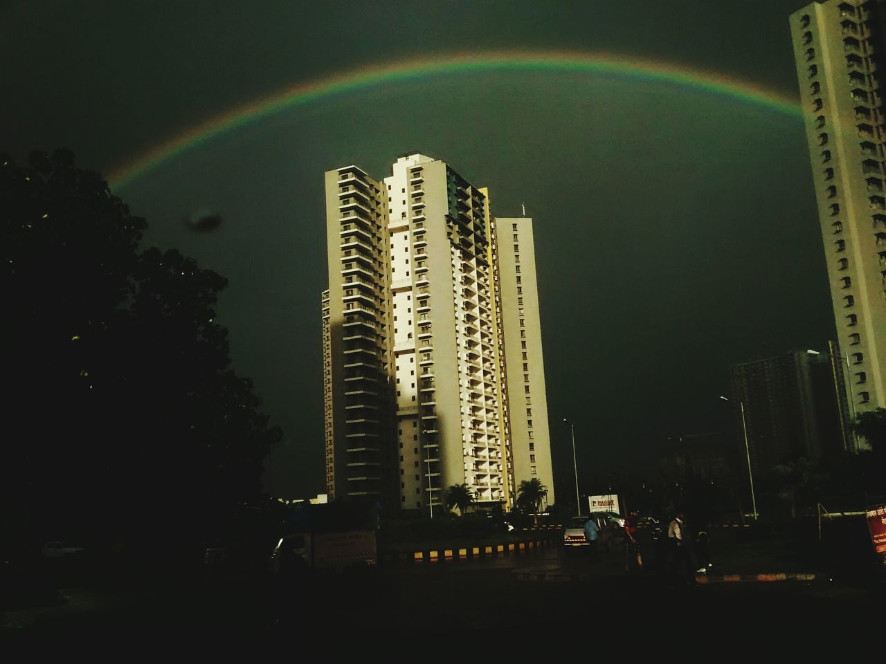 architecture, building exterior, built structure, tall - high, skyscraper, city, travel destinations, rainbow, no people, outdoors, cityscape, low angle view, modern, illuminated, nature, day, tree, sky, beauty in nature