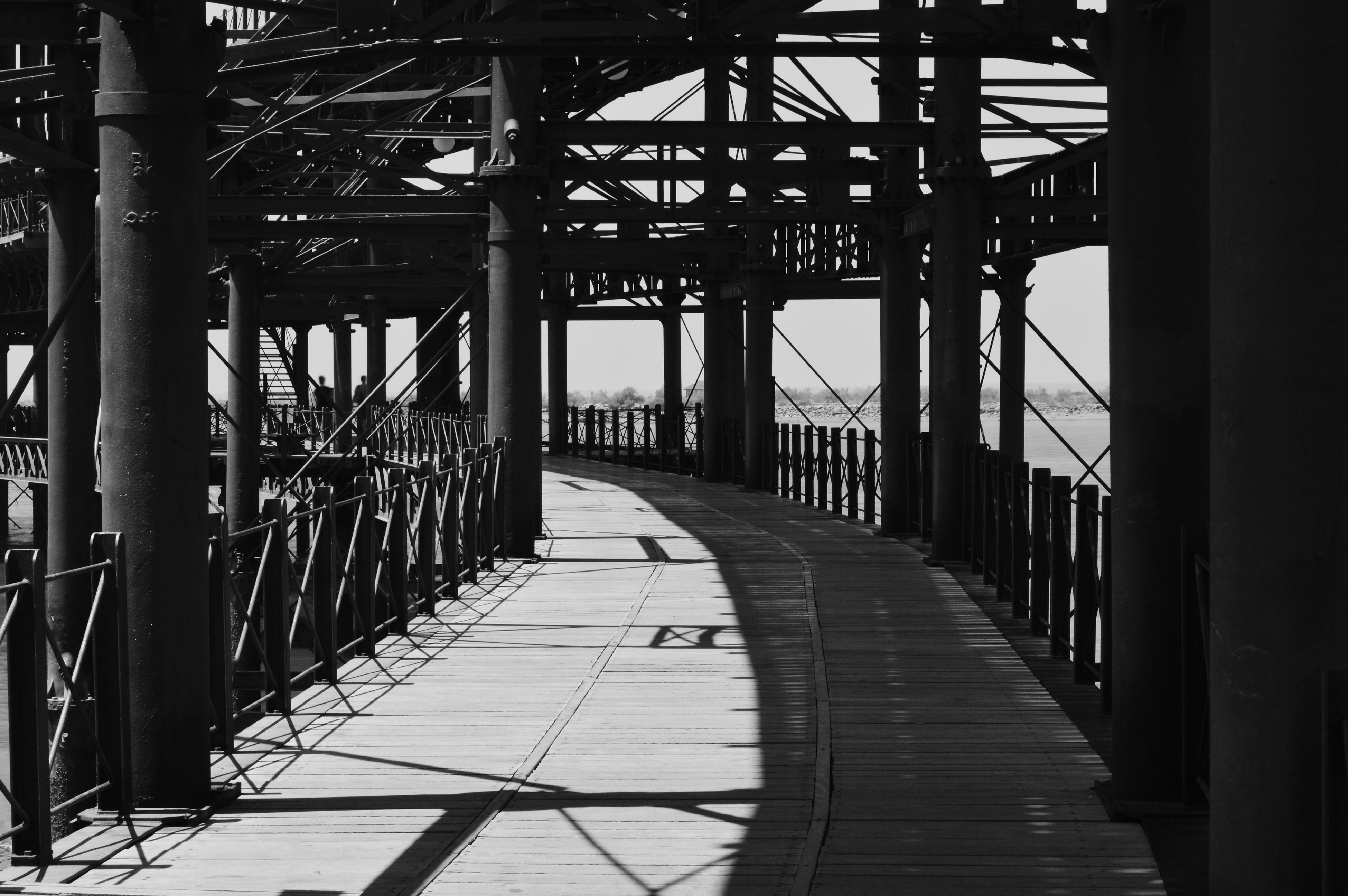 bridge - man made structure, connection, architecture, built structure, engineering, sunlight, transportation, the way forward, bridge, travel destinations, day, shadow, architectural column, no people, footbridge, outdoors, sky