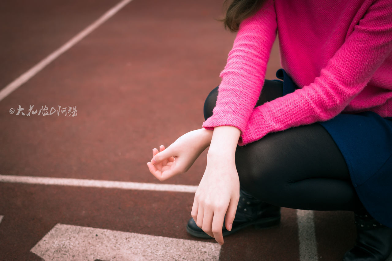 real people, lifestyles, one person, outdoors, day, running track, leisure activity, low section, sports clothing, human hand