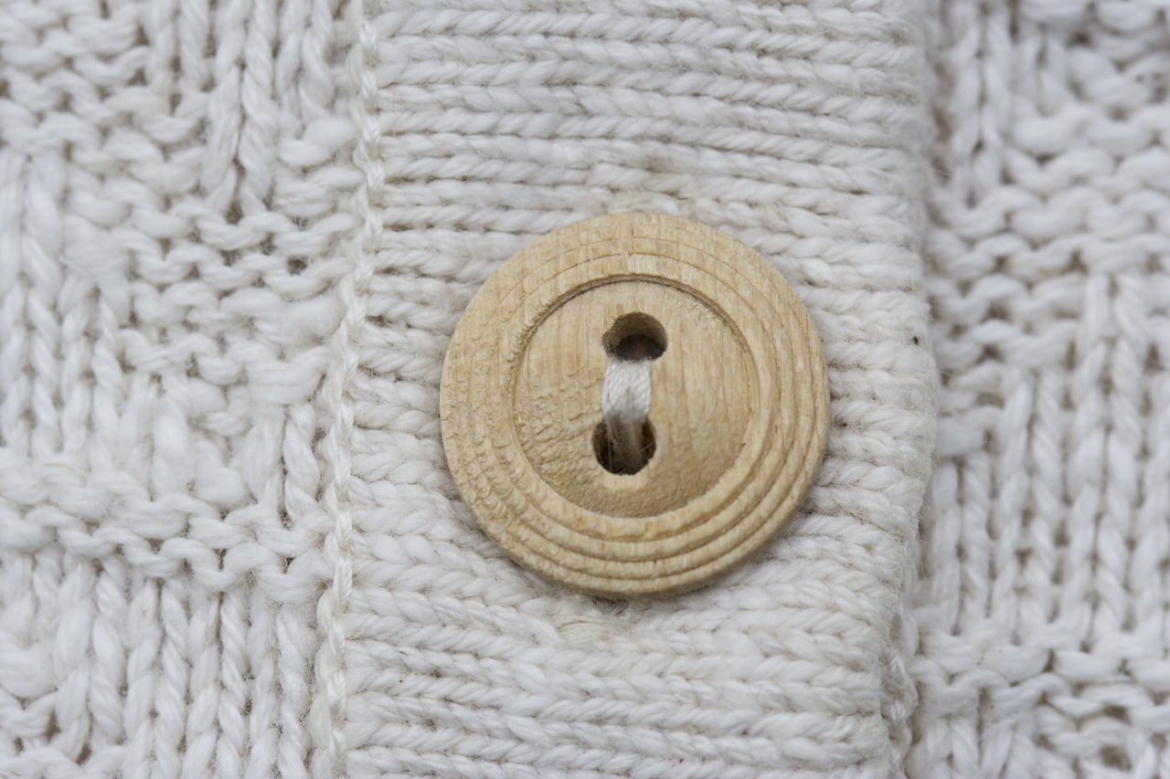 wooden button on knitwear - knitting pattern with purls and knits Background Backgrounds Built Structure Close-up Cotton Detail Fashion Knitted  Knitting Knitting Knitwear Material Natural Natural Materials No People Pattern Softness Sweater Textile Textile Industry Warm Clothing Wood - Material Wooden Wool Woolen