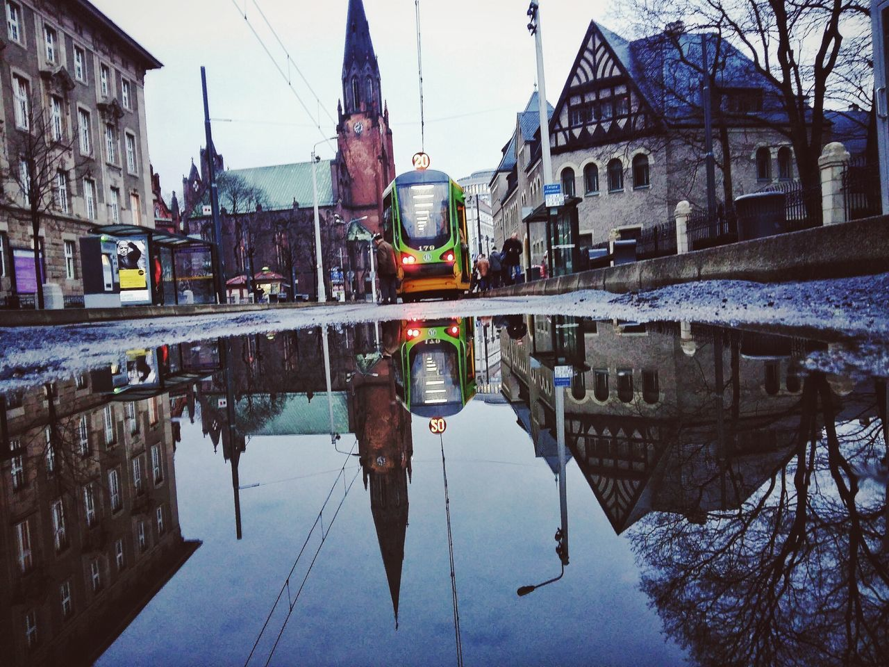 architecture, building exterior, built structure, reflection, transportation, mode of transport, outdoors, water, day, winter, city, nautical vessel, cold temperature, no people, clear sky, sky, puddle