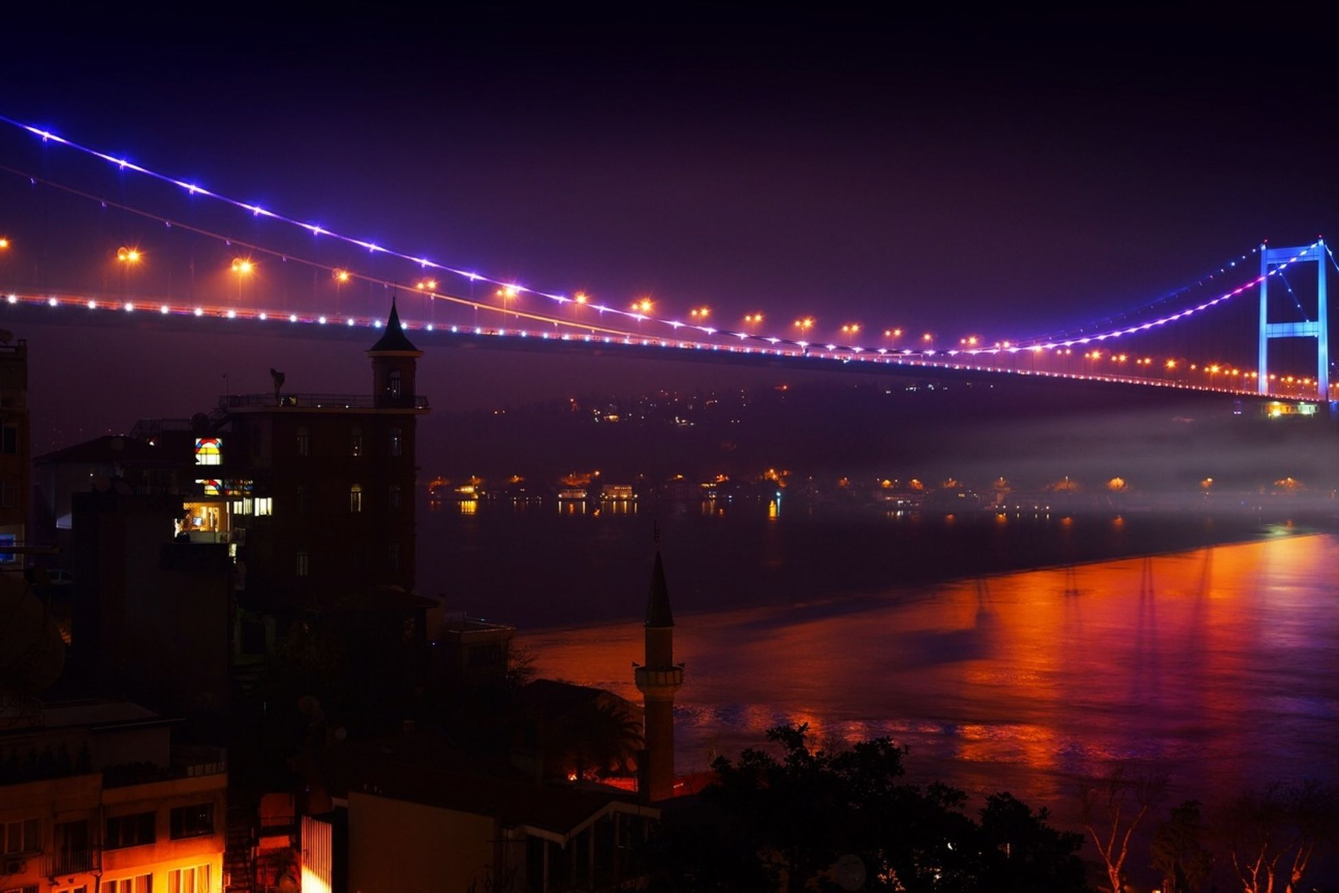 illuminated, architecture, night, built structure, connection, bridge - man made structure, water, bridge, river, engineering, building exterior, city, suspension bridge, sky, reflection, waterfront, dusk, travel destinations, transportation, copy space