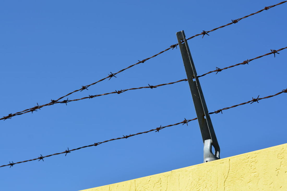 Barbed Wire Protection Clear Sky Danger Low Angle View No People Business Finance And Industry Outdoors Close-up Sky Day Minimalism Clear Sky Against Blue Sky Barbed Wire Keep Out Security Confined  Confinement Confined  Backgrounds Minimalist Architecture
