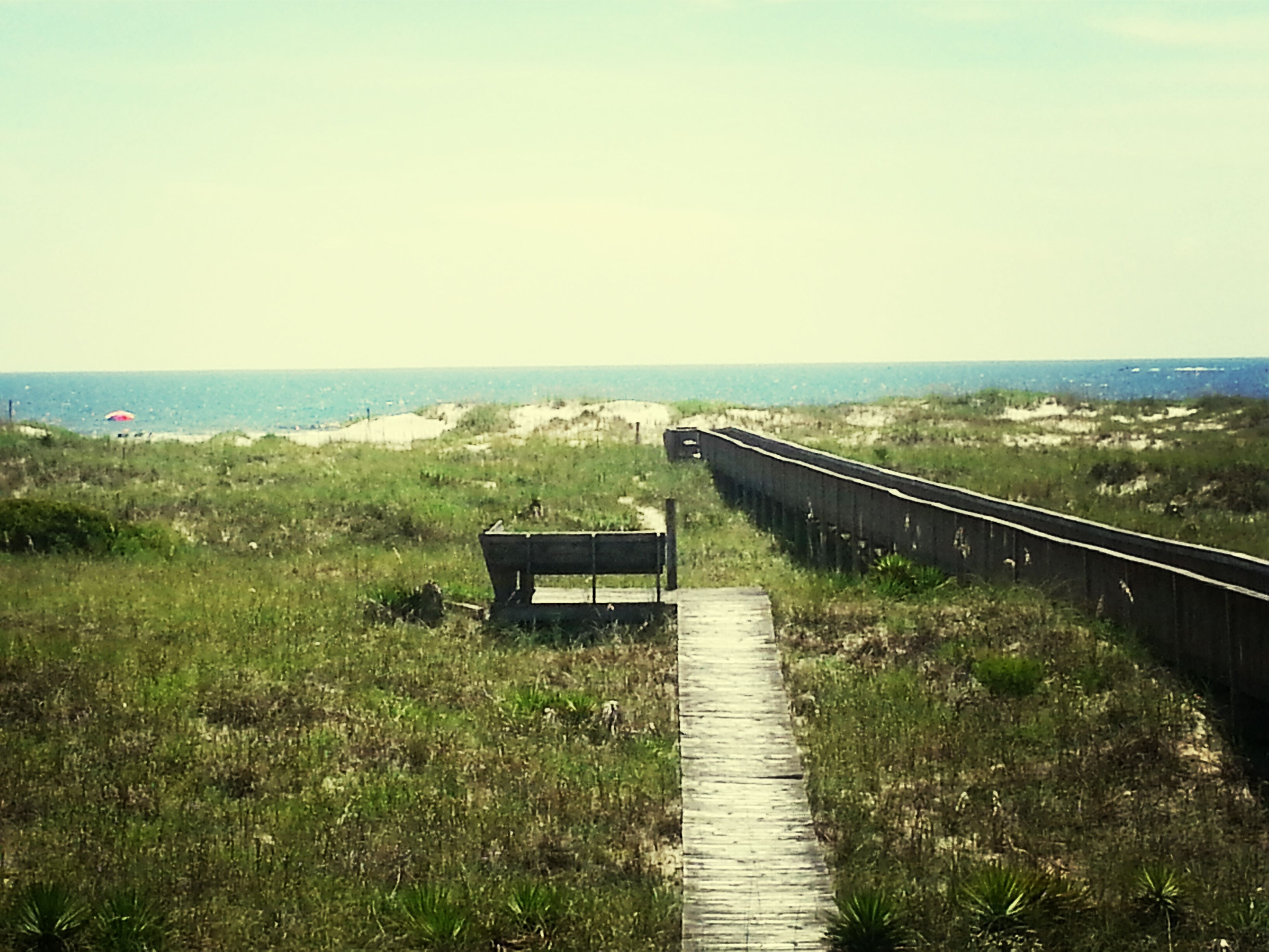 horizon over water, railing, tranquil scene, tranquility, sea, the way forward, water, scenics, grass, nature, sky, beauty in nature, clear sky, high angle view, landscape, plant, diminishing perspective, narrow, idyllic, outdoors