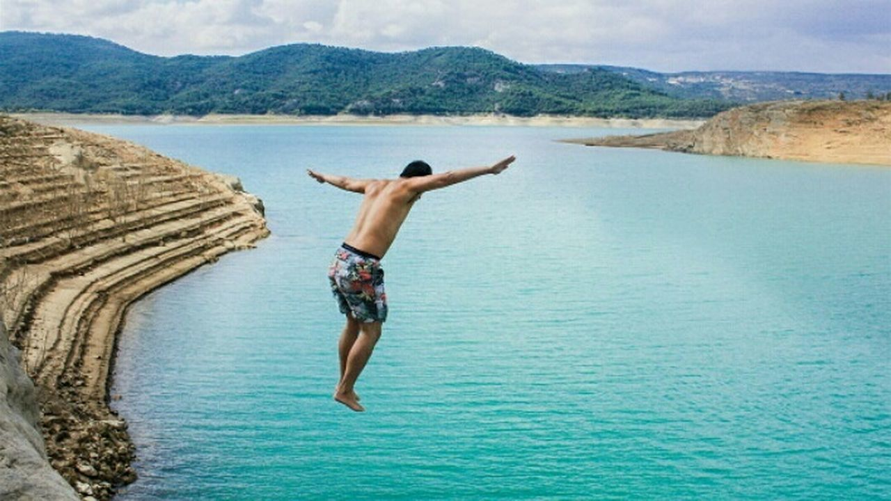 one man only, arms raised, rear view, one person, only men, full length, day, adults only, shirtless, mid-air, water, men, outdoors, mountain, adult, jumping, sea, nature, people, beauty in nature, sky