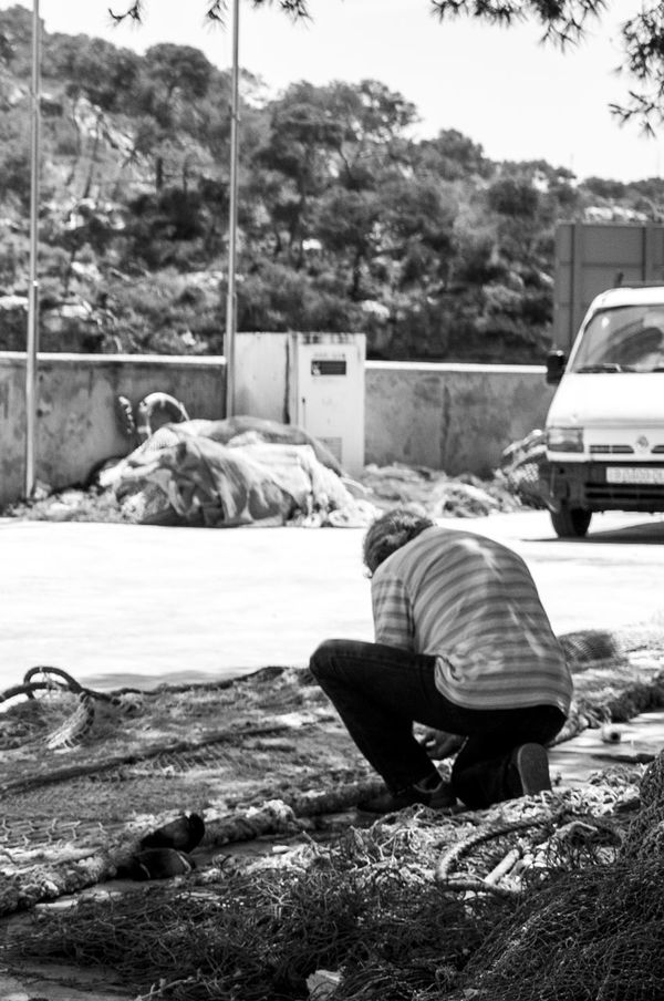 A local fisherman repairing nets Day Full Length Mammal Men Nature Occupation One Person Outdoors People Real People Rear View Fishing Fishing Village Harbour Mallorca Cala Figuera Labour Work Occupations Black And White The Portraitist - 2017 EyeEm Awards